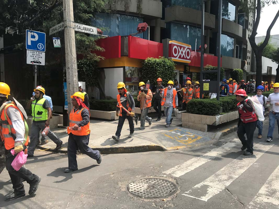 Volunteers march down a street in the Roma neighbourhood heading to a collapsed building after the earthquake in Mexico City.
