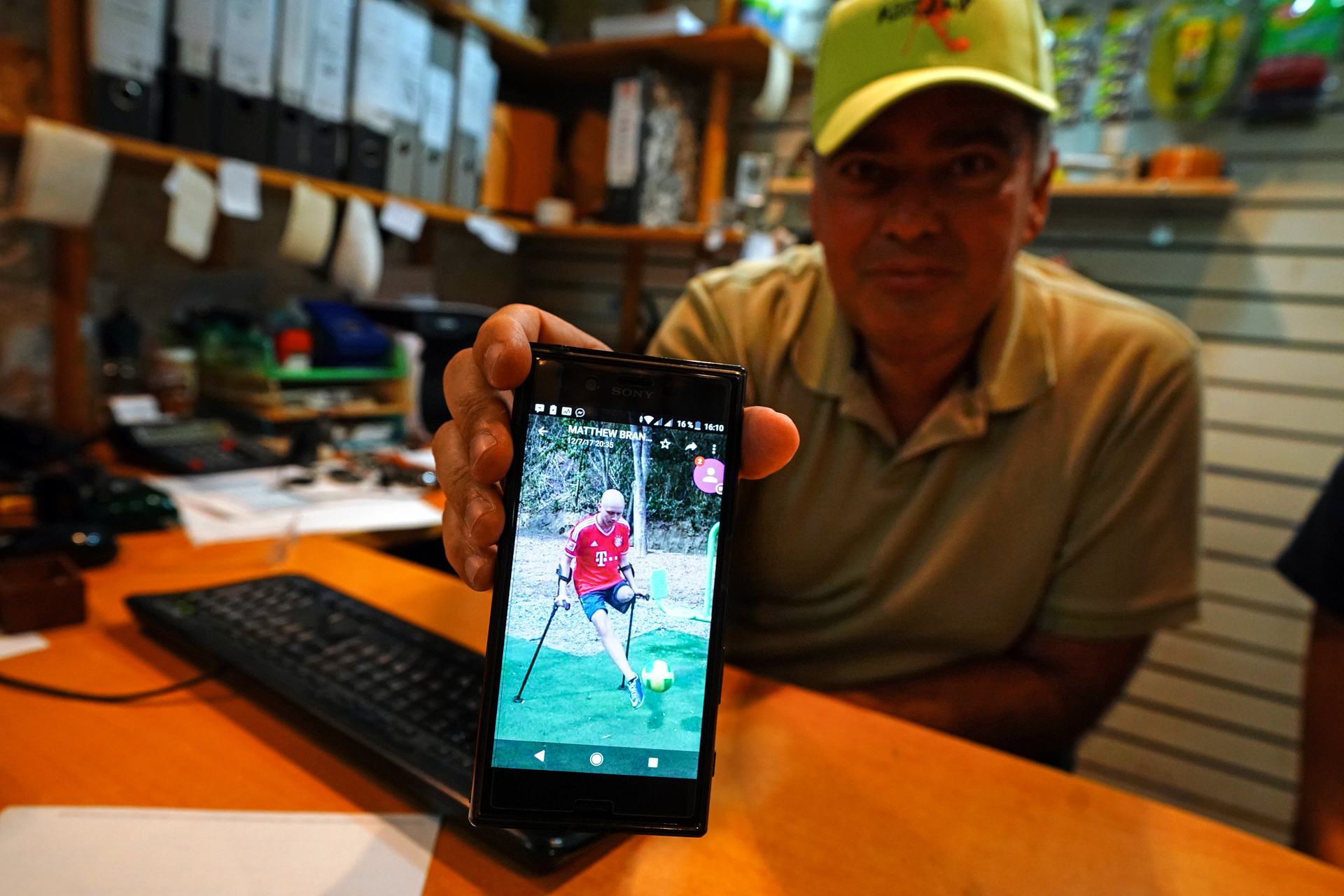 A man at a desk shows a photo on his phone of his son kicking a football on crutches
