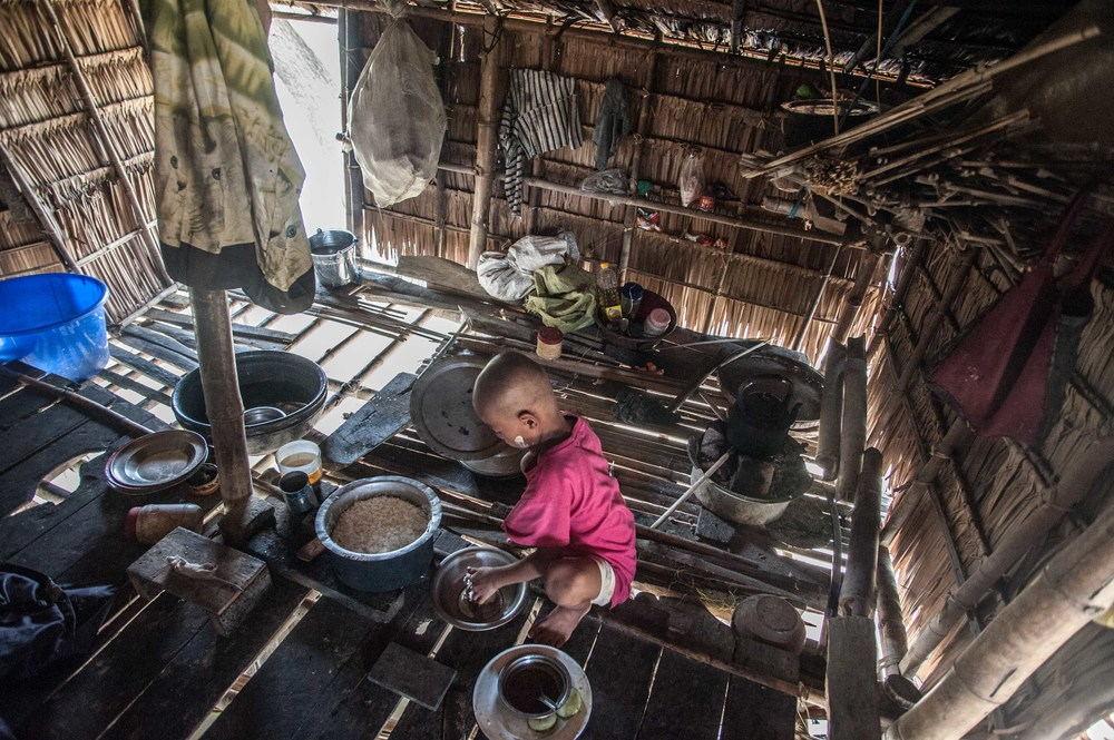 A child is alone in the center of a room helping to prepare food.