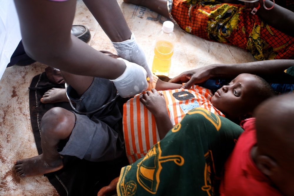A Burundian refugee suspected of having cholera receives IV rehydration in the health clinic at Lake Tanganyika Stadium in Kigoma, Tanzania.