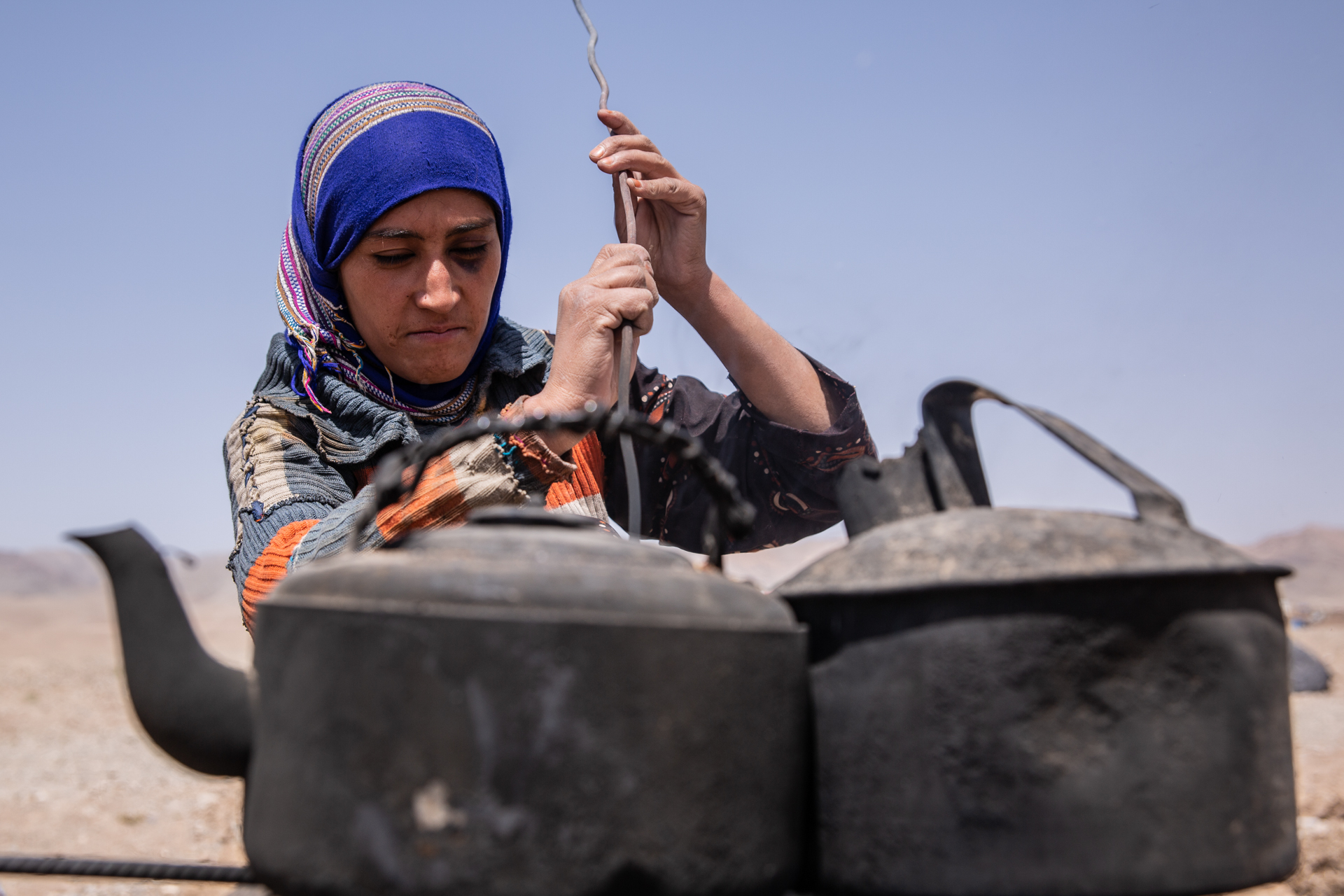 A woman behind two tea pots in a camp in Afghanistan