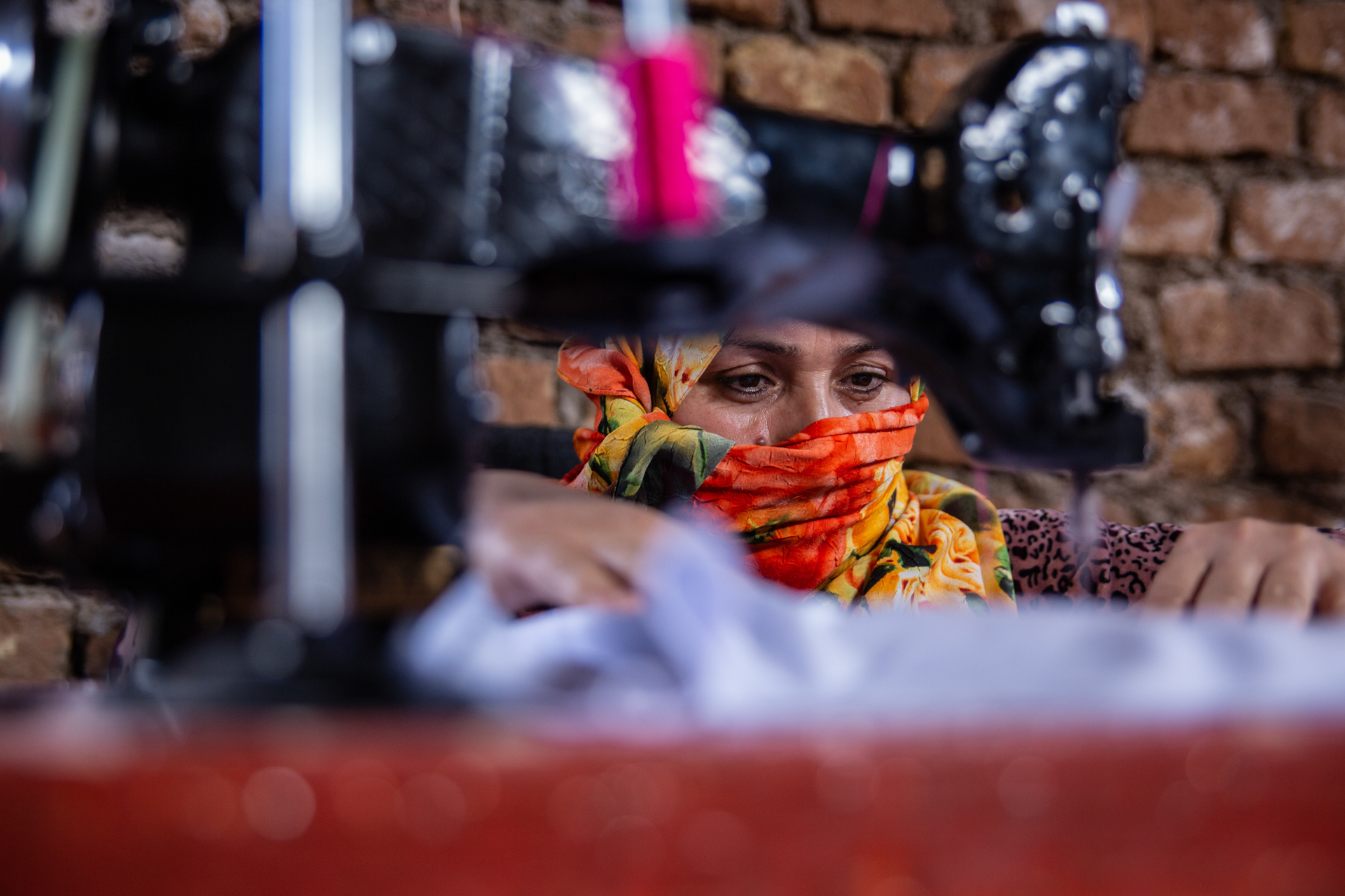 A woman in Afghanistan sits behind a sewing machine