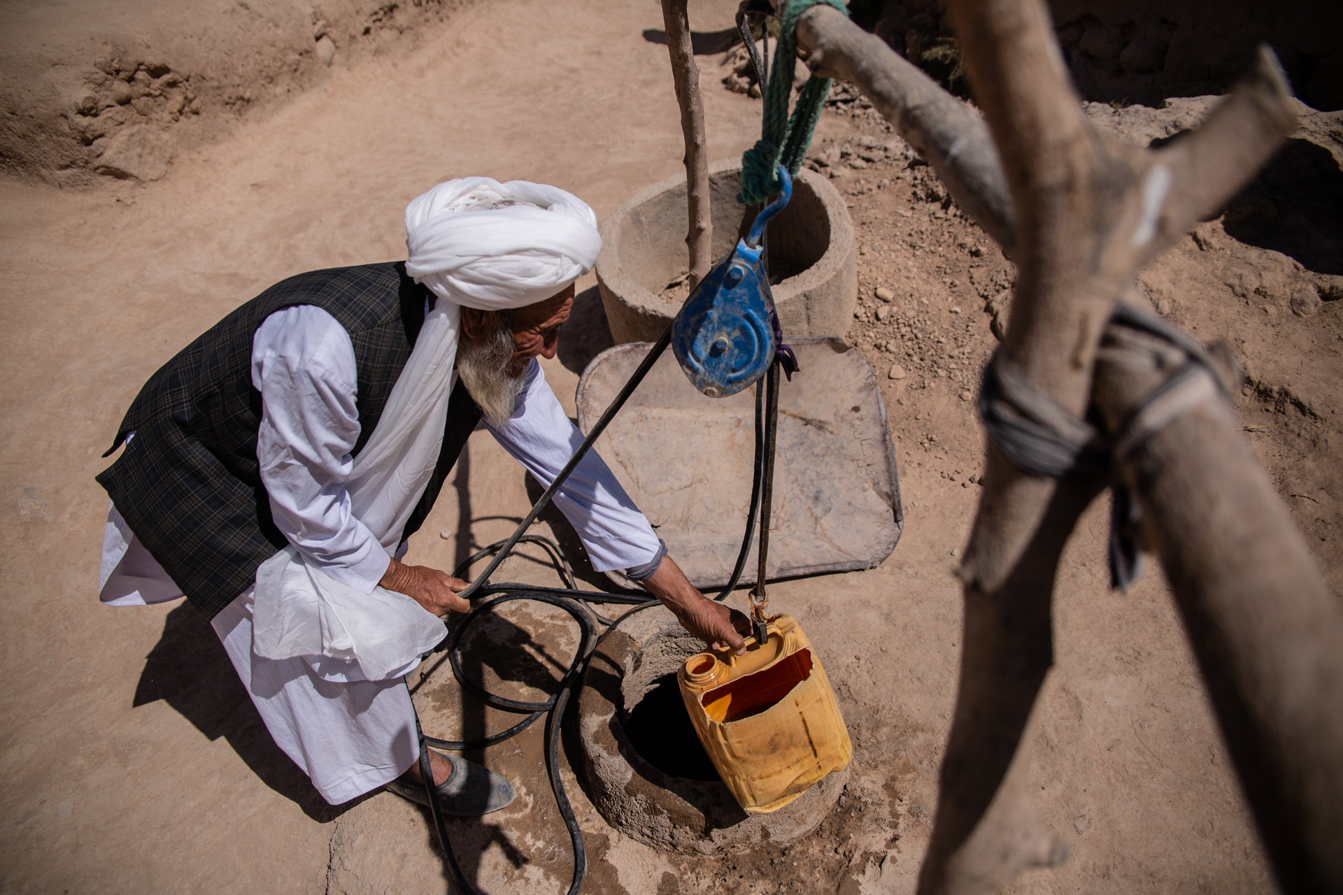 An older man in Afghanistan draws water from a well