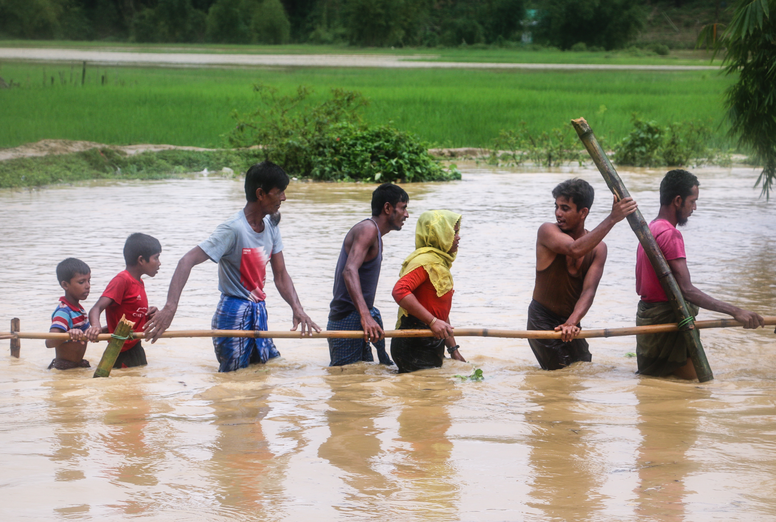 Refugees walk across a flooded field