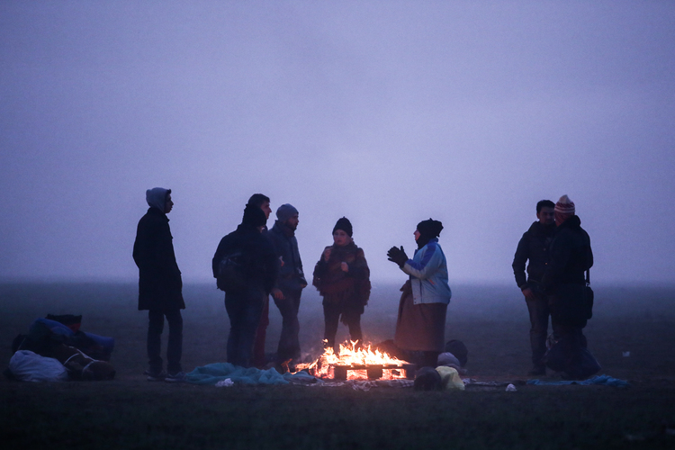 A Syrian family warming themselves at a fire camp