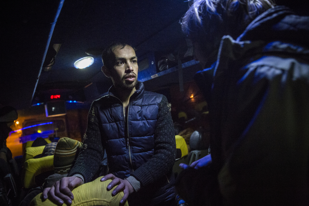 Shafiullah Muzaffar, 23, helps a German volunteer to communicate with the other Afghan refugees