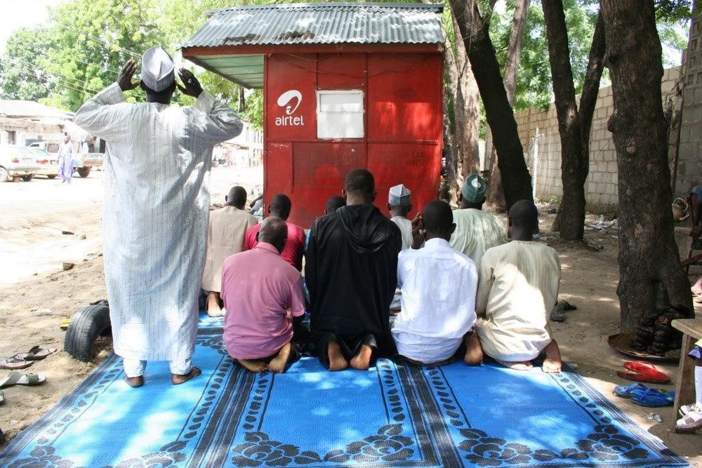Men in Nigeria pray outside