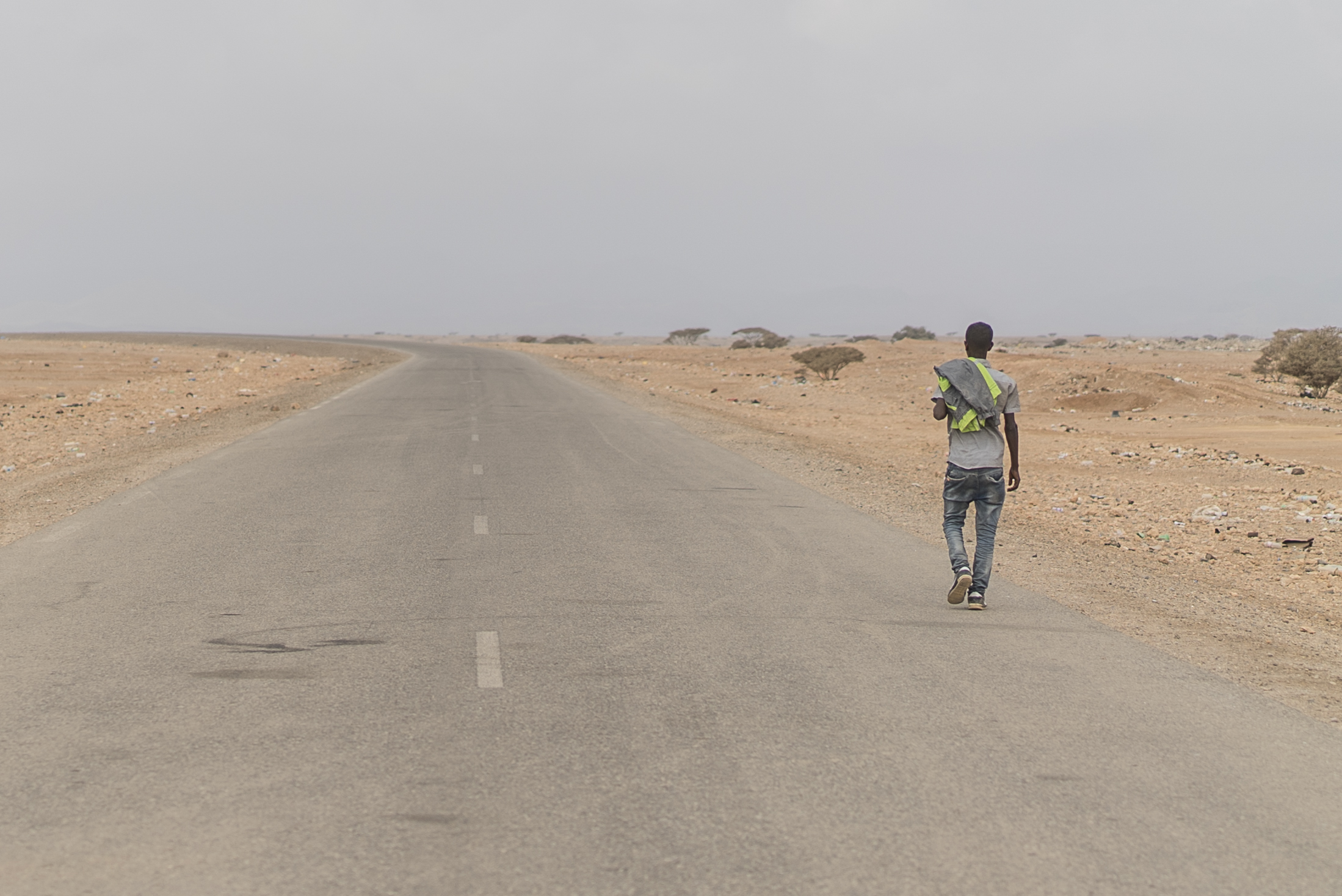 A man walks away from camera down an outstretched road in a desert scene
