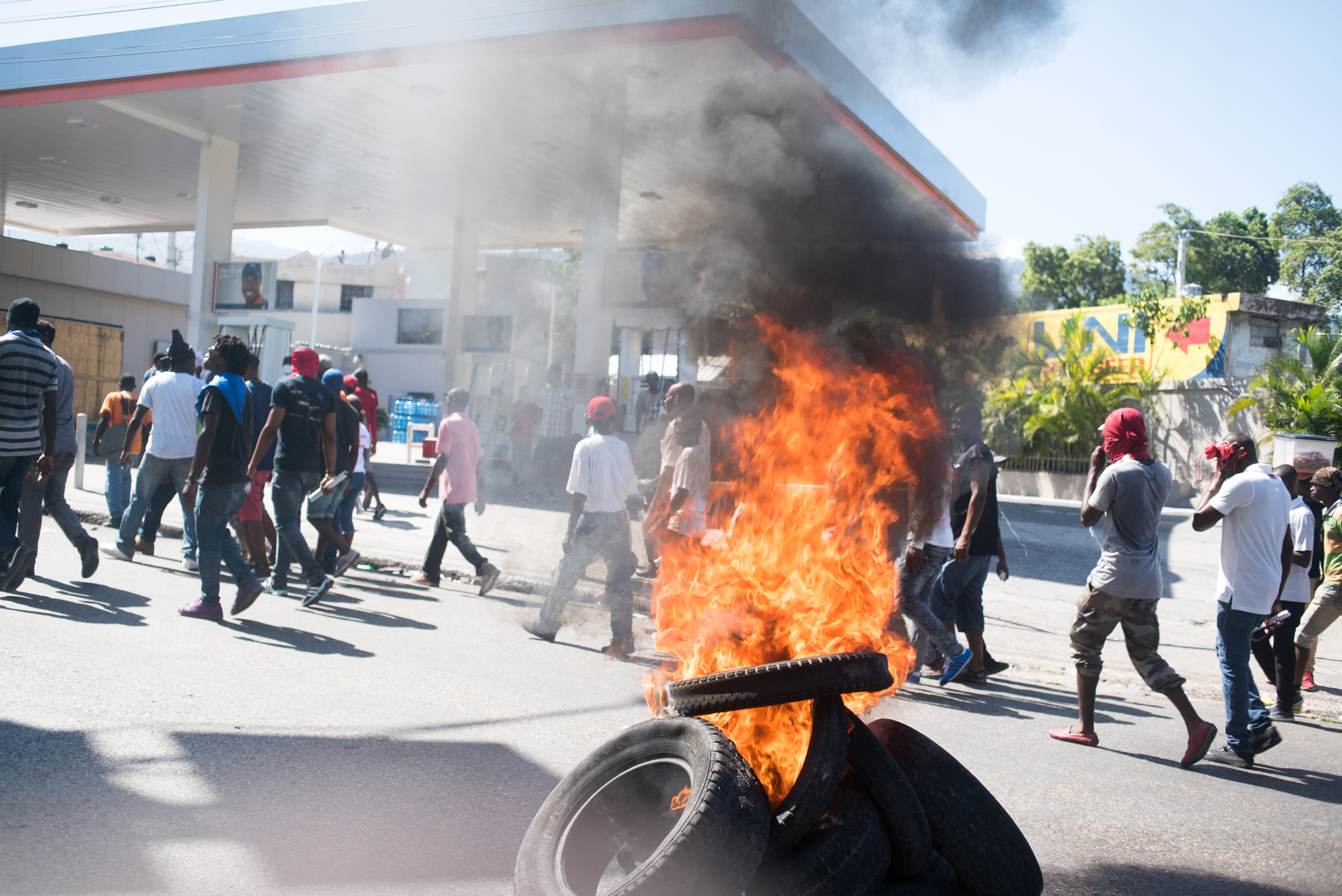 A stack of tires on fire at a petrol station as protesters march behind