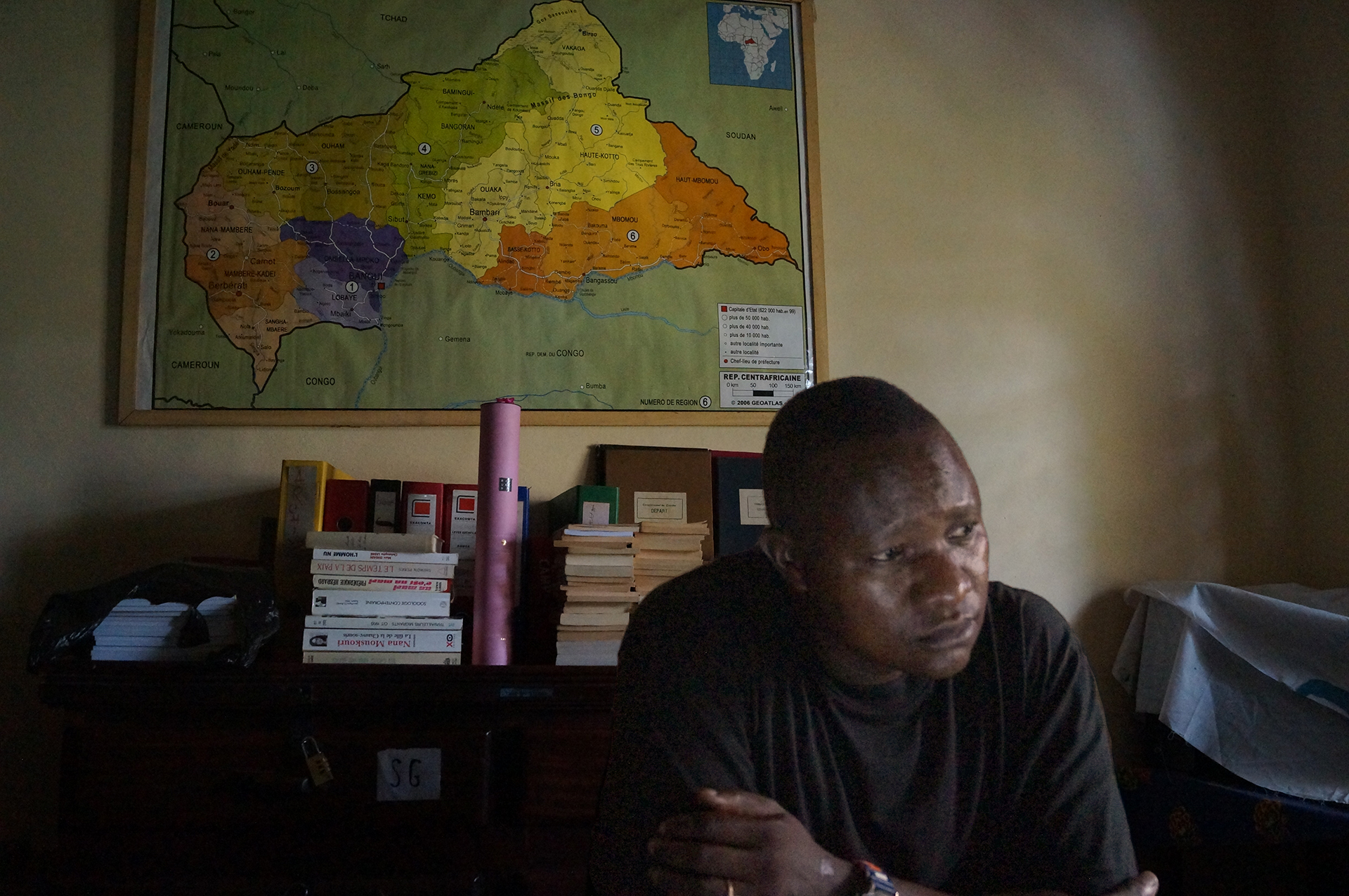 The young priest Frederic Nakombo sits in his office filled with case files, books and a large map of the Central African Republic on the wall behind him.