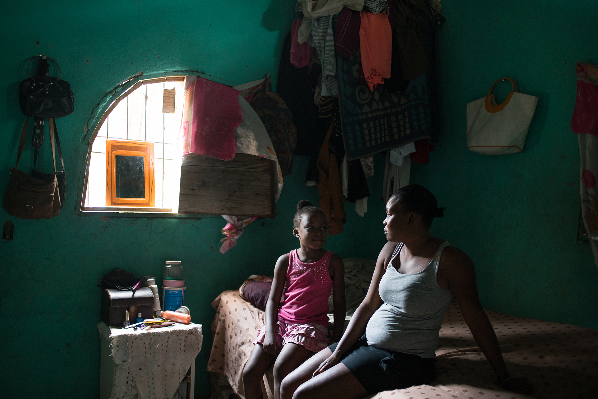 A mother and daughter sit on a bed as light from the window falls on them
