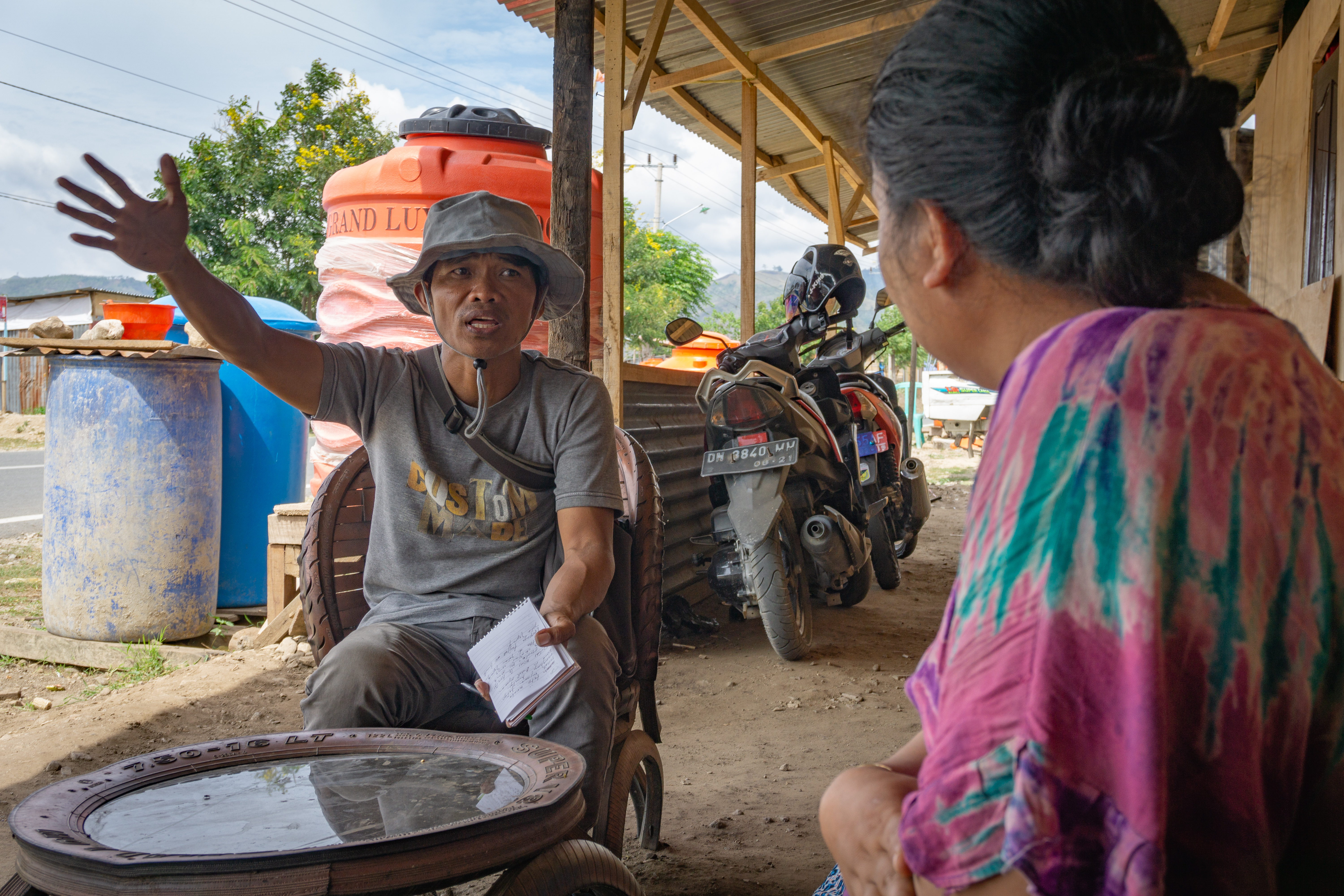 Local journalist Yardin Hasan interviews a family who built their own wooden shelter on the outskirts of Palu, Indonesia