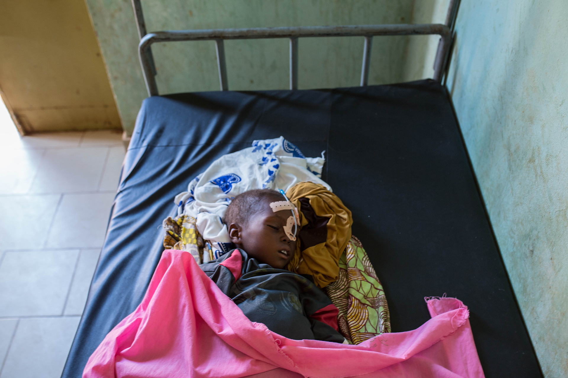 A young child with medical equipment on a bed