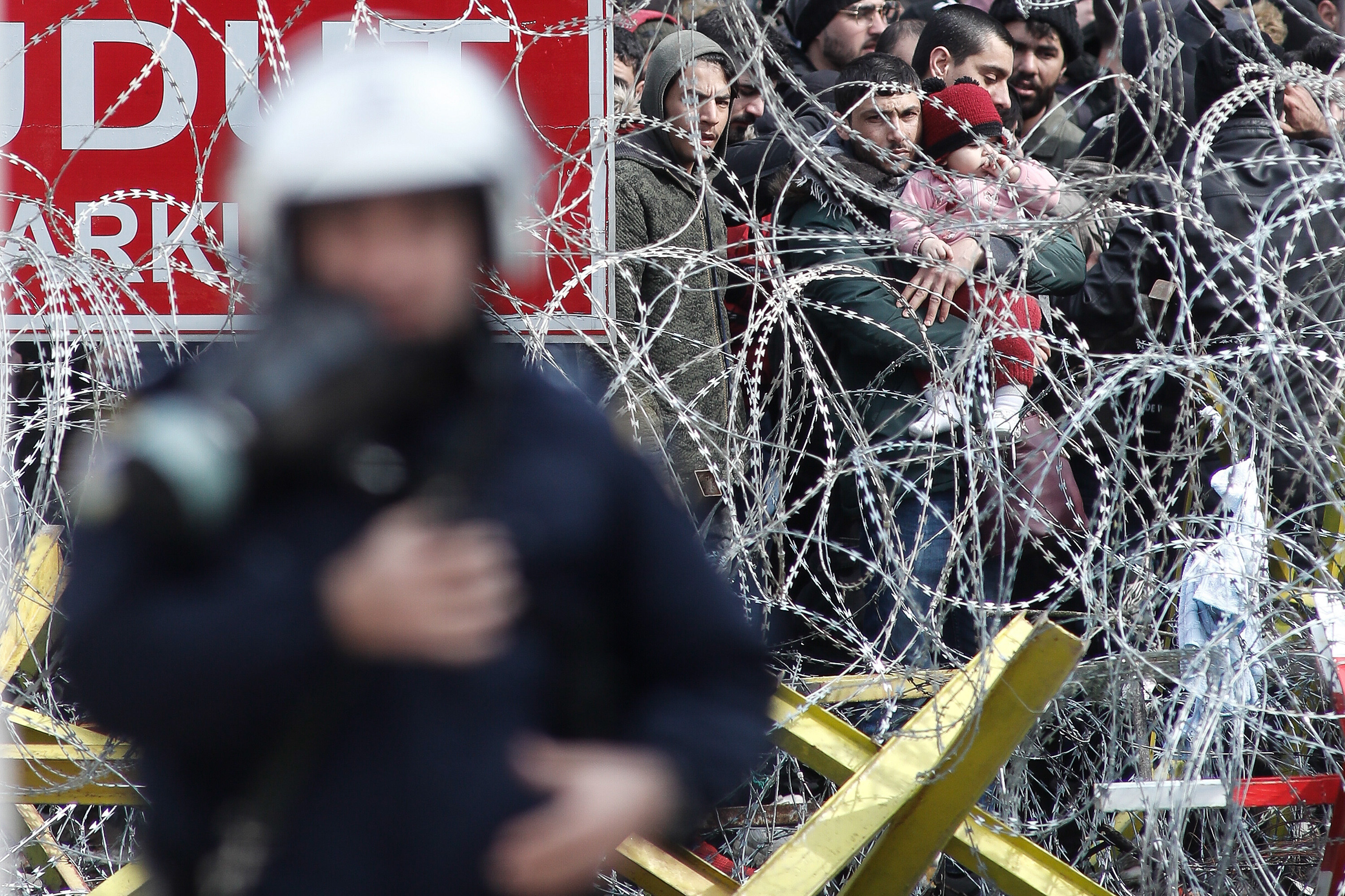 A photo of Greek riot police patrol along a barbed-wire fence. Asylum seekers gather on the other side of the fence.