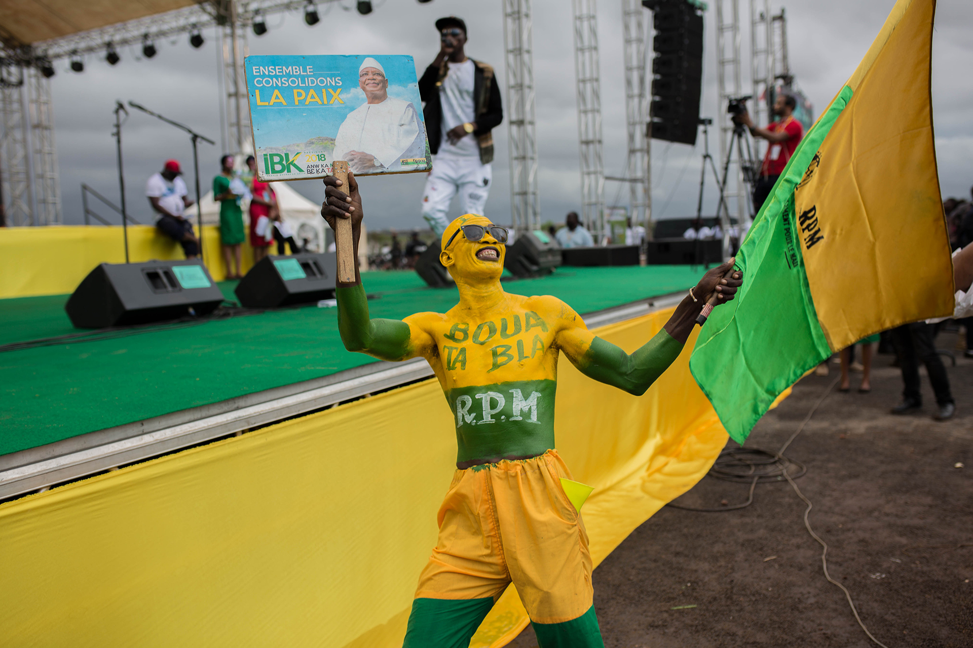 A person covered in green and yellow body paint waves a banner at a political rally.