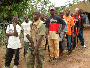 [Liberia] Former MODEL fighters line up to hand in their weapons at the newly opened in disarmament camp in Zwedru, Liberia in July 2004.