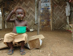[Liberia] A young child sits in front of her hut eating. She is one of 10's of thousands of IDPs displaced by years of war and reliant on food distributed by WFP. [Date picture taken: 2005/07/08]