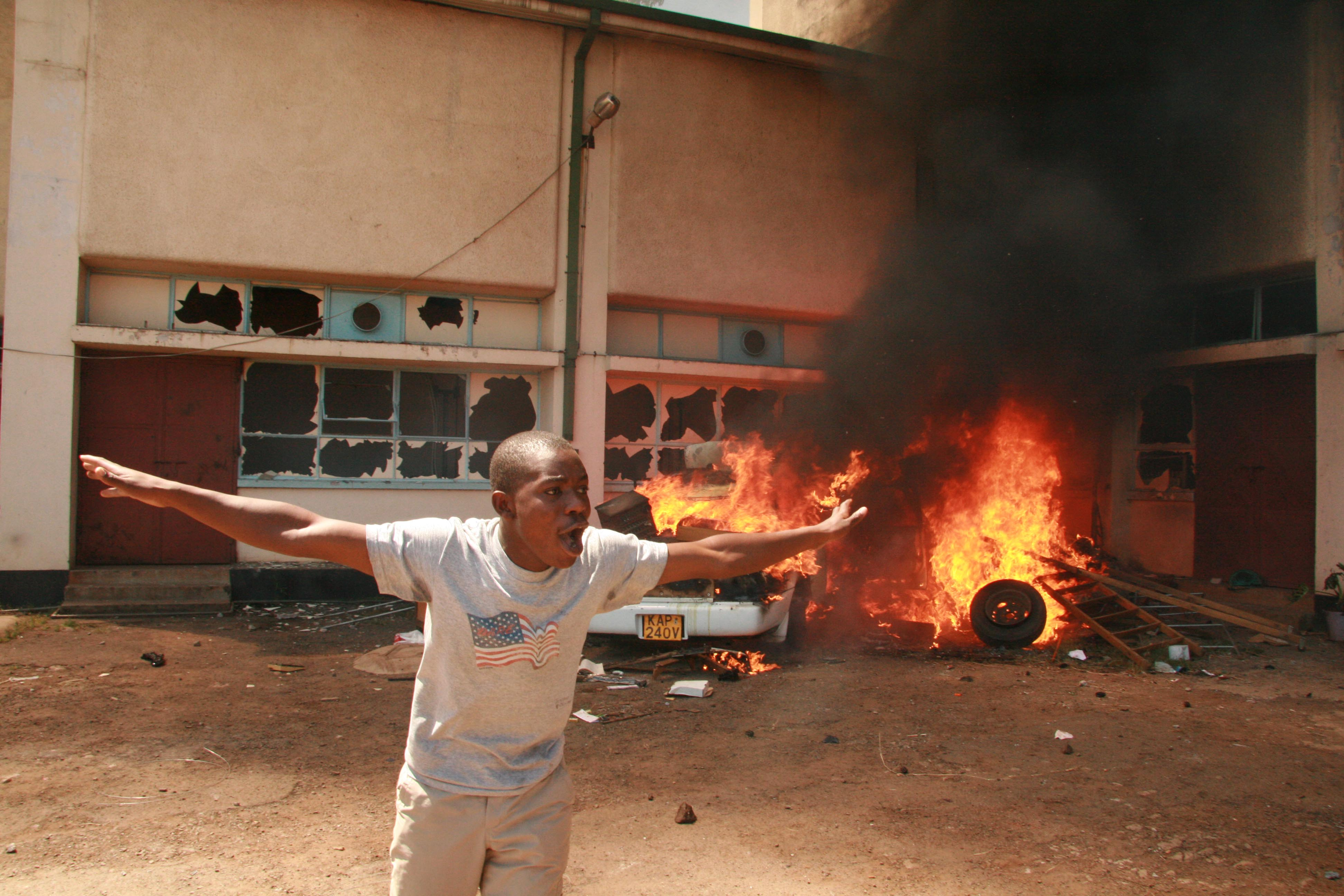A demonstrator runs from a burning car set on fire by irate youths after  a  funeral service called by opposition ODM was tear-gassed by police, Ligi Ndogo, Kenya, January 2008.
