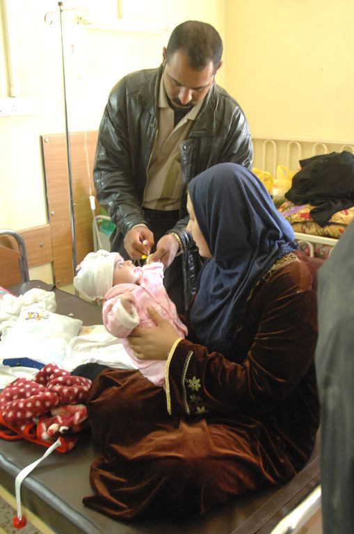 A mother holds her sick baby while an Iraqi doctor gives the child an IV at the Children's Hospital in Muqdadiyah, Iraq. New aid money will go to the most vulnerable Iraqis