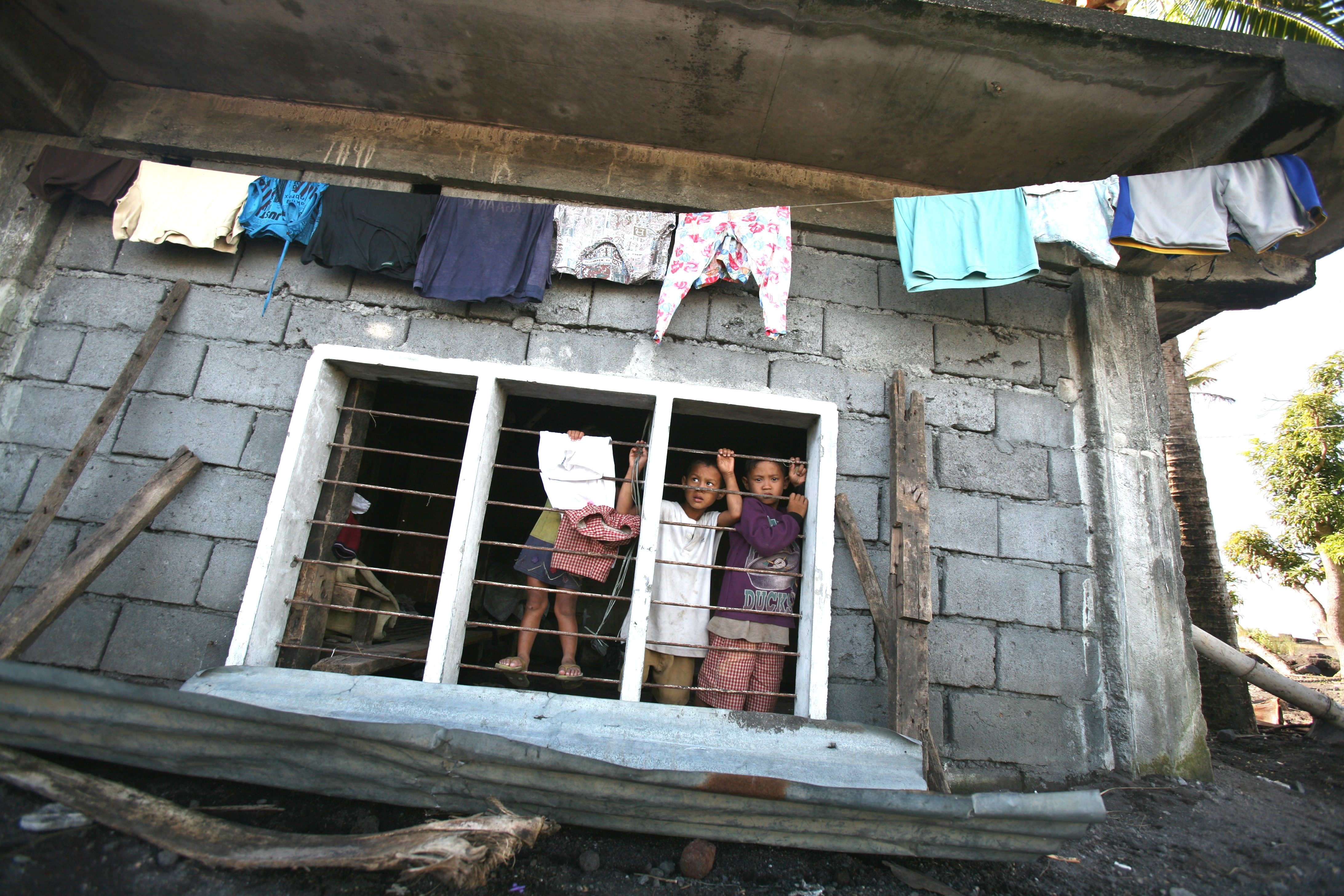 Children in a house damaged by typhoon, Maypon village in the Philippines