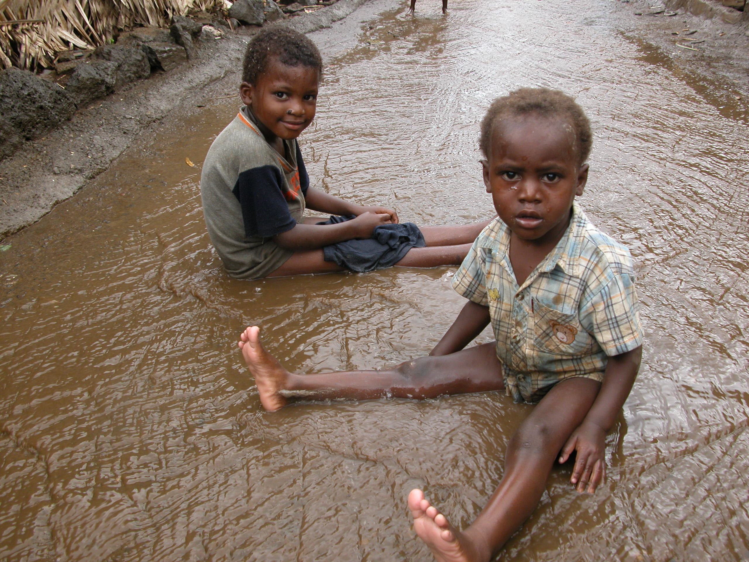 Children play in the rain on streets of Barakani, on the Comoros island of Anjouan
