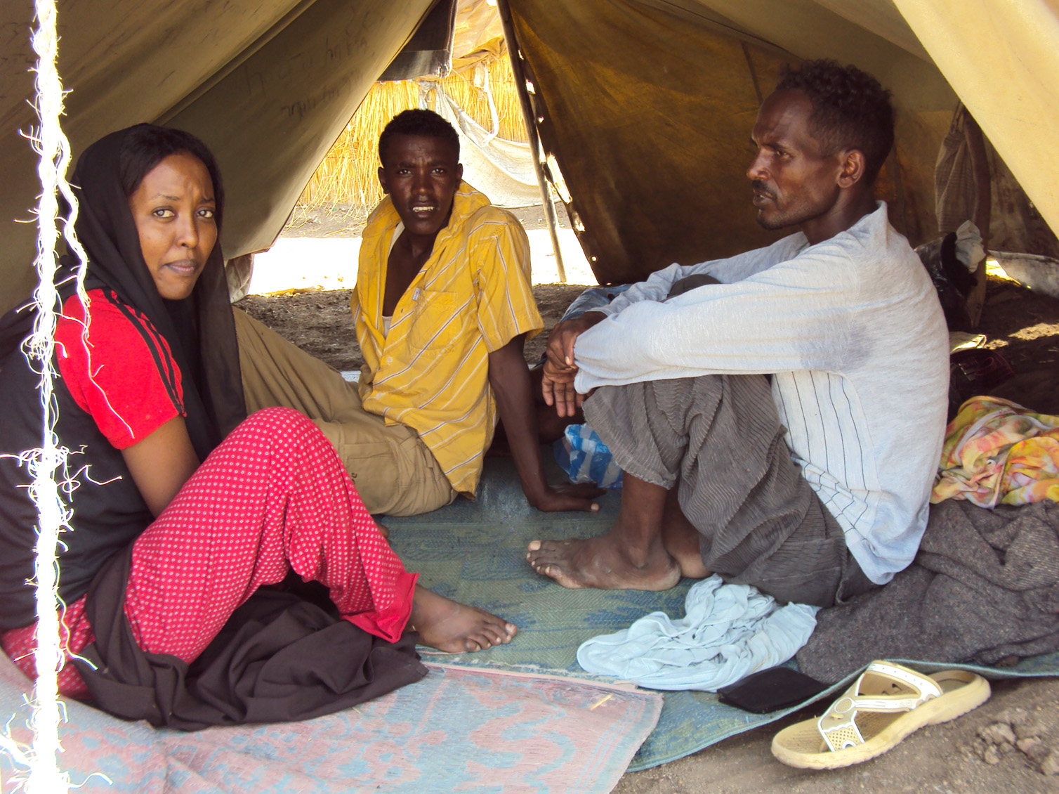 Shagarab Camp - Turmesgy Gabr Selassie (right) fled the Eritrean army 3 months ago. He shares this tent with 11 other men and women where they sleep on the ground. The only luxury in their tent is the thin sheets with which they cover themselves