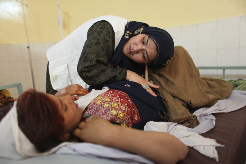A midwife listens to the fetal heartbeat in the belly of an expectant mother at Boost hospital, Helmand Province