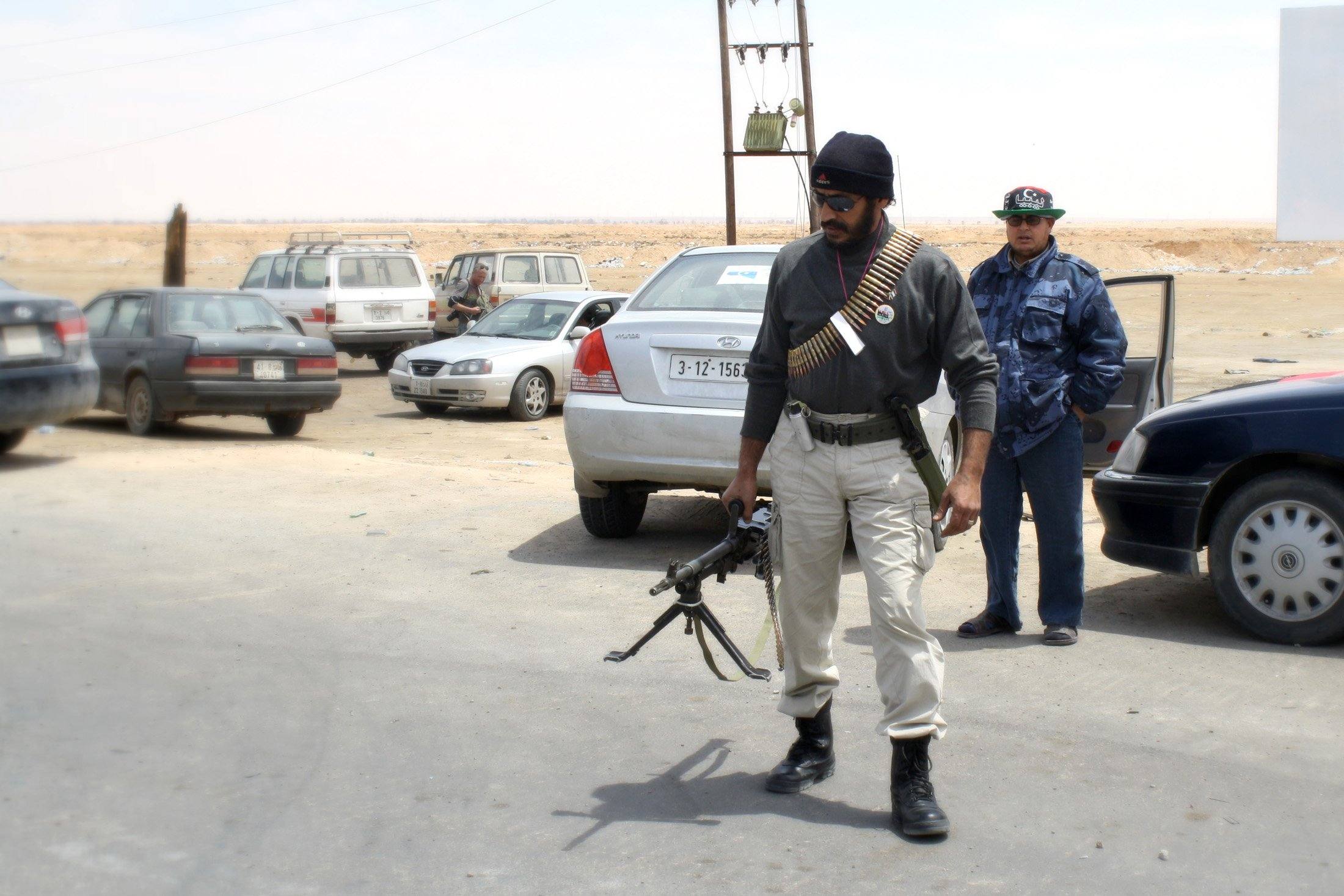 A Libyan rebel fighter arrives by car at the last checkpoint before the frontline, between Ajdabiya and Brega