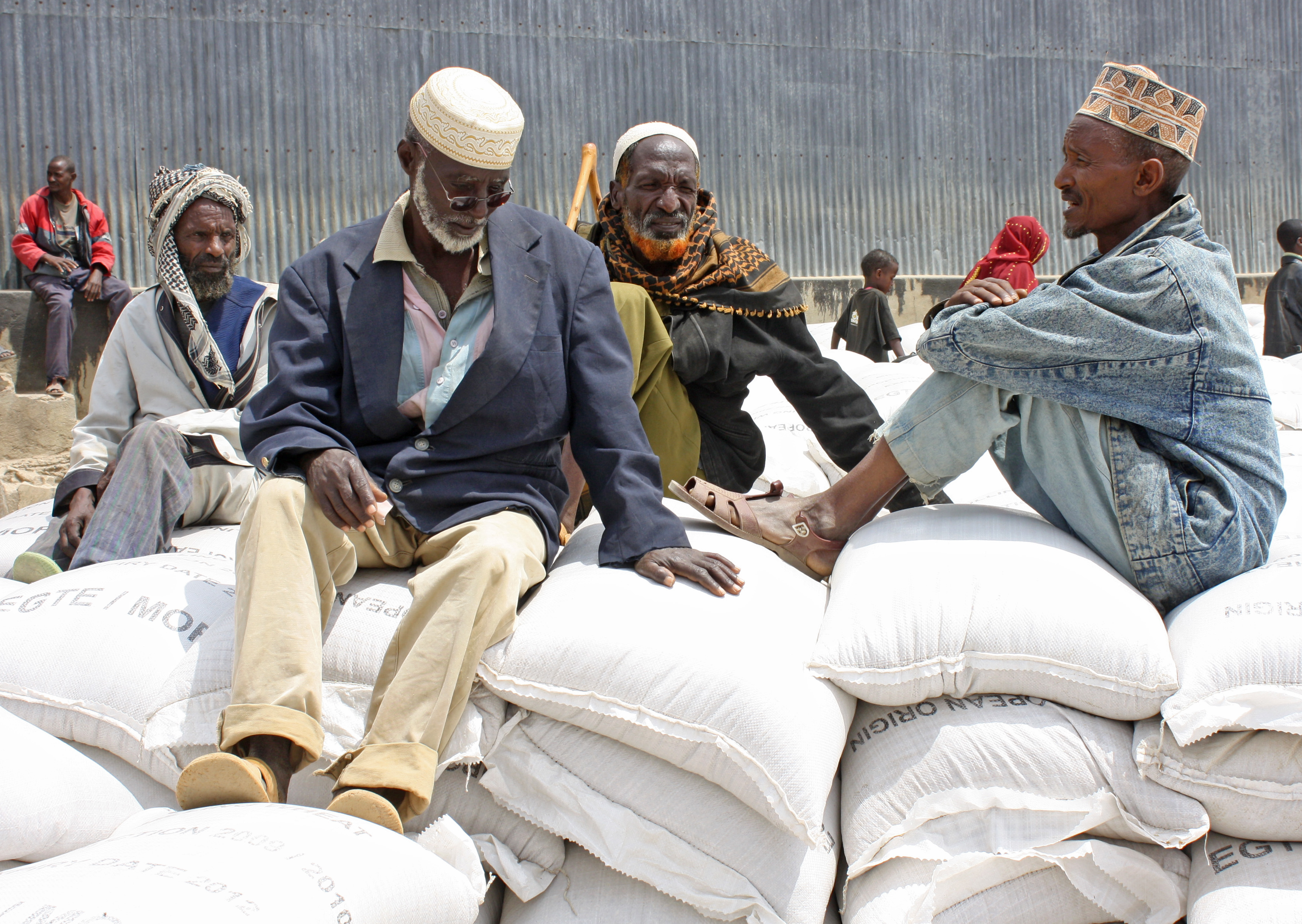 The elderly await their share while sitting on piles of sacks filled with cereal for aid hand-outs under the Productive Safety Net Programme in the Borena zone in Ethiopia's Oromiya region