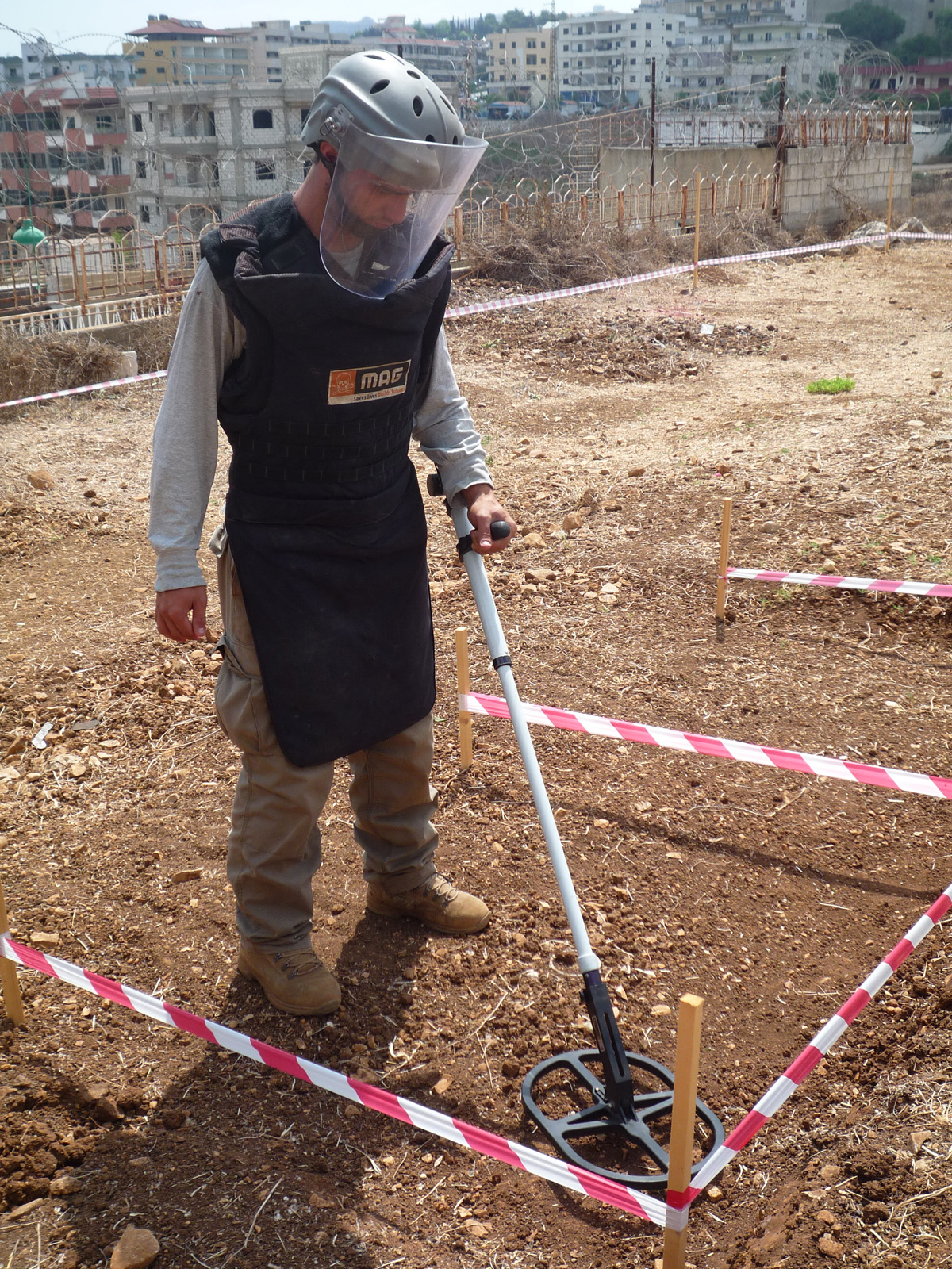 A deminer with the  Mines Advisory Group, a British non-governmental organization, searches for cluster munitions near in Kfar Joz, South Lebanon