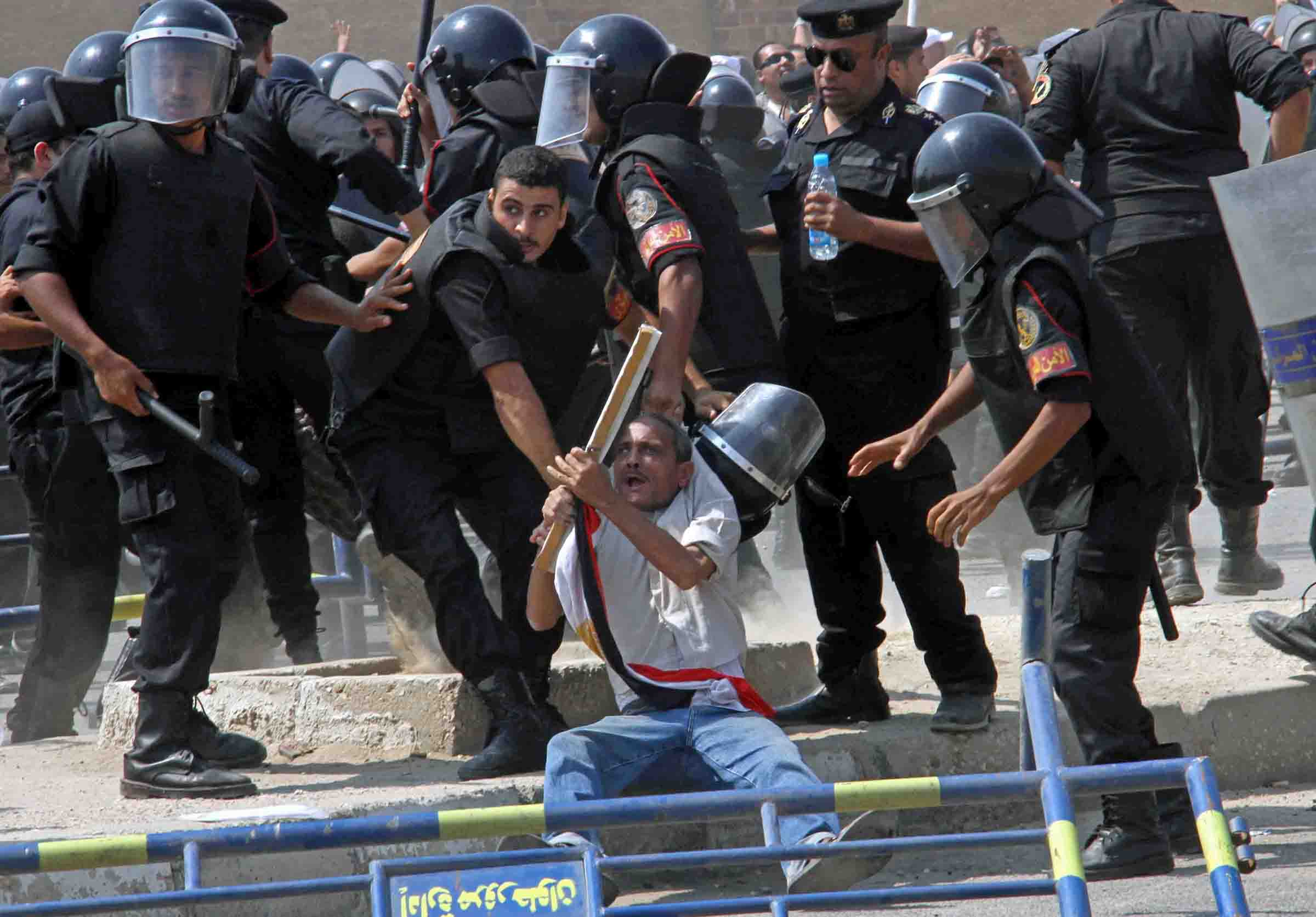 Policemen suppress opposition demonstrators in Cairo