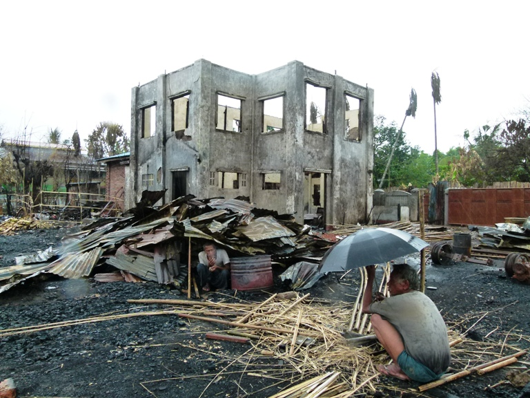 Two men sit under the the remnants of their homes in Sittwe, the capital of Myanmar's Rakhine State, following violence in June 2012.