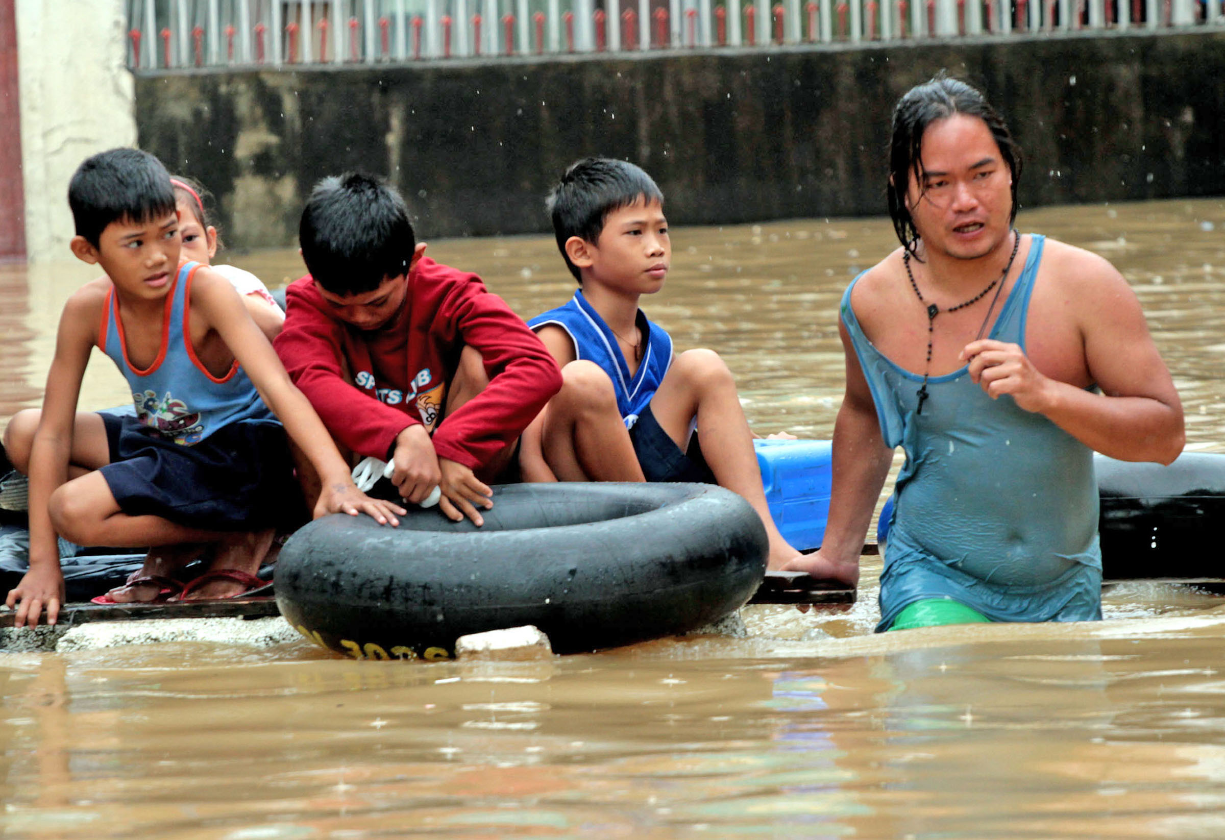 Young boys are rescued using inner tubes at a flooded riverside community in Manila, Philippines
