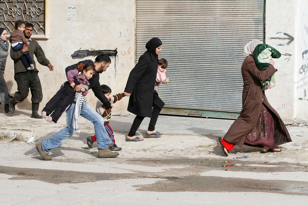 Civilians flee from fighting after Syrian army tanks entered the northwestern city of Idlib, Syria, Tuesday, Feb. 14, 2012