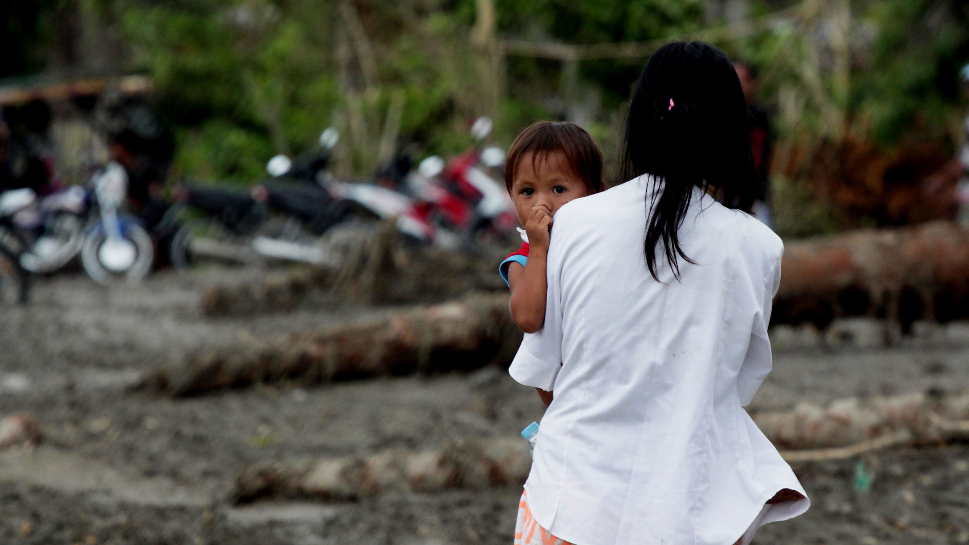 A mother and her young child return to their devastated farming village in Mindanao. Typhoon Bopha struck the island on 4 December 2012, devastating livelihoods for millions