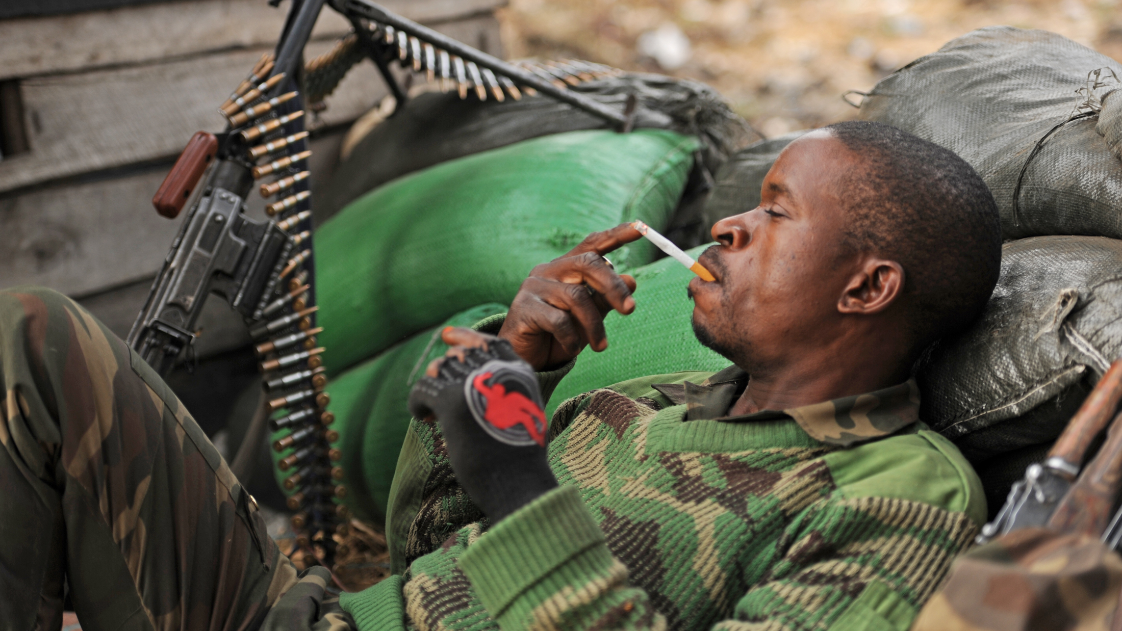 An FARDC soldier has a cigarette on the Kanyaruchinya frontline on the outskirts of the eastern DRC city of Goma