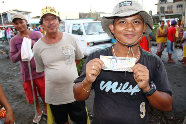 Bernard Morteja, 34, just received 500 pesos for one days work cleaning up debris and rubble off the streets of Tacloban from Taiwan-based Buddhist Tzu Chi Foundation, one a number of cash-for-work initiatives launched in the city in the aftermath of Typh
