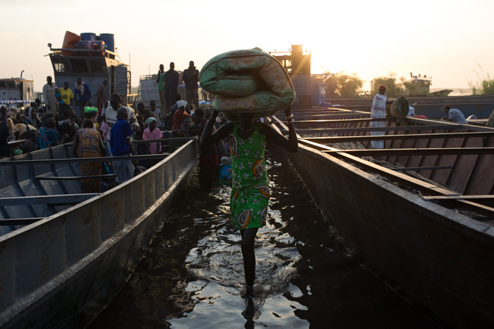 A lady carries her belongings as she disembarks from a boat from Bor, arriving at an informal settlement of internally displaced persons in the town of Mingkamen in Awerial county, South Sudan, on January 11, 2014. According to latest figures from the Uni