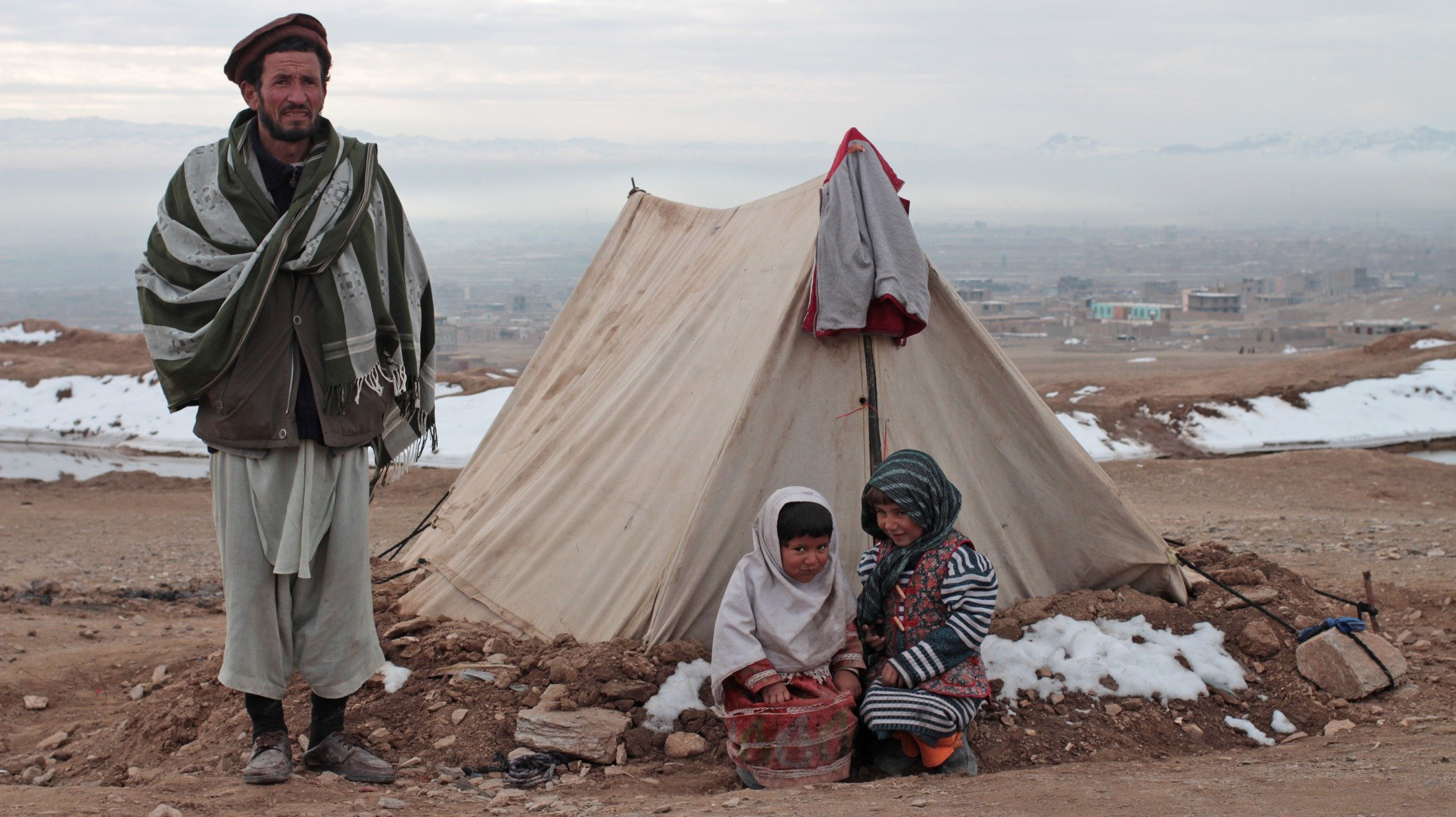 Displaced families from Ghor province in Afghanistan shelter outside Herat in freezing temperatures
