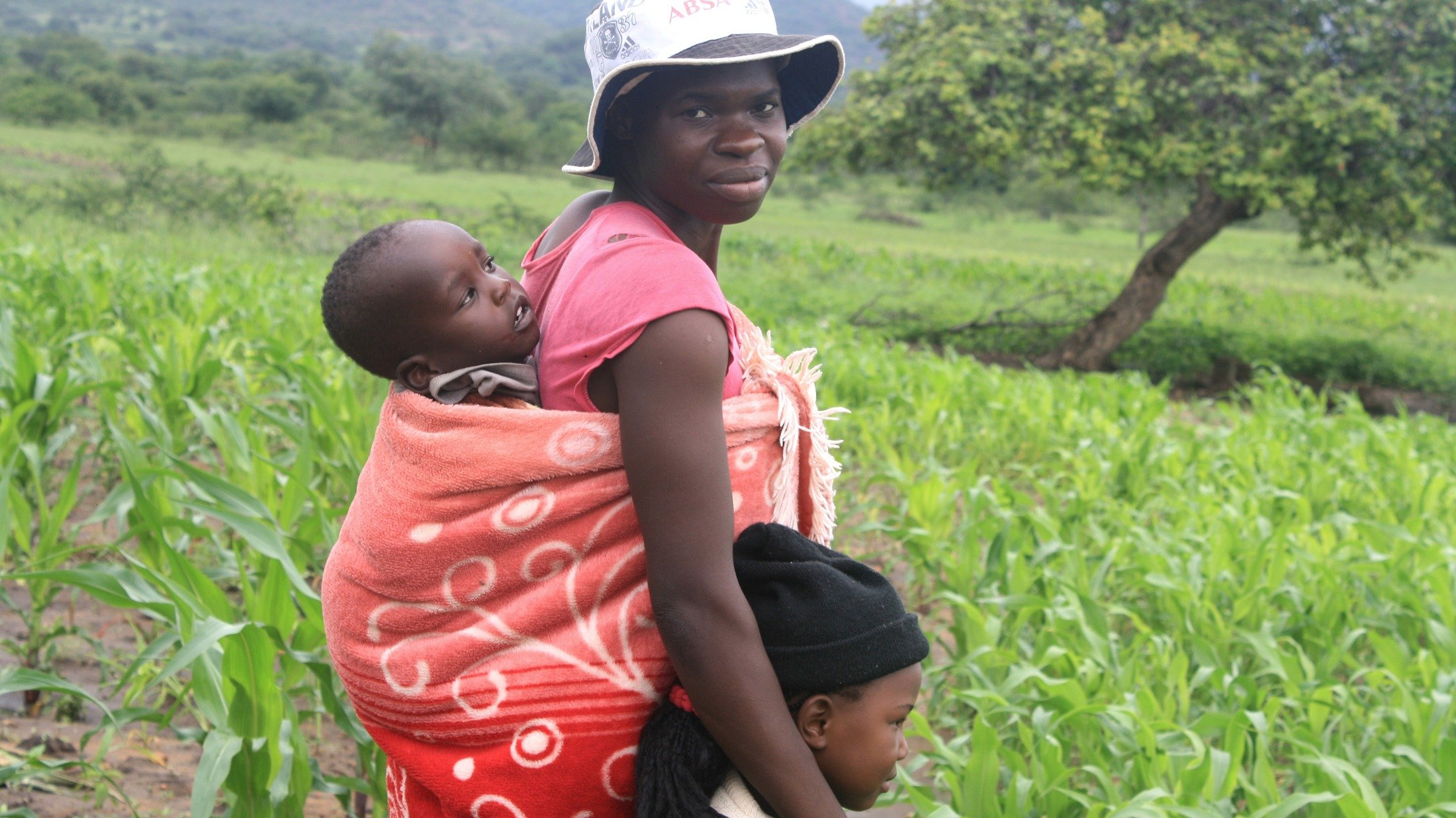 Eugenia Musakanda, with her two children at her field in the Sipamphi area in Zimbabwe's Masvingo province