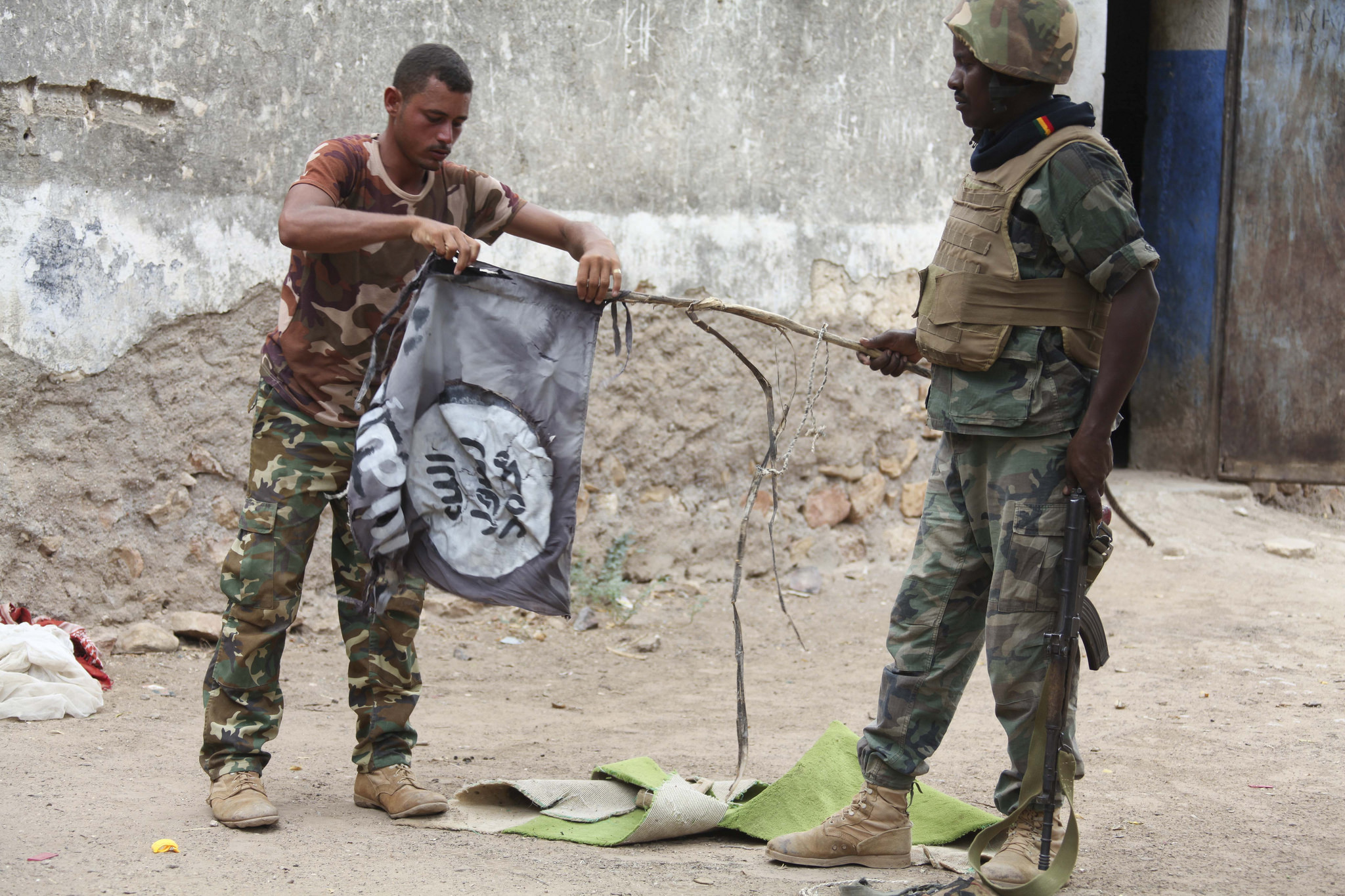 Djiboutian soldiers destroy an al Shabaab flag after the town of Bula Burde was liberated by AMISOM forces on 16th March 2014