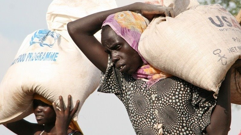 A welcome burden: women sweat under the weight of rations distributed at the Doro refugee camp