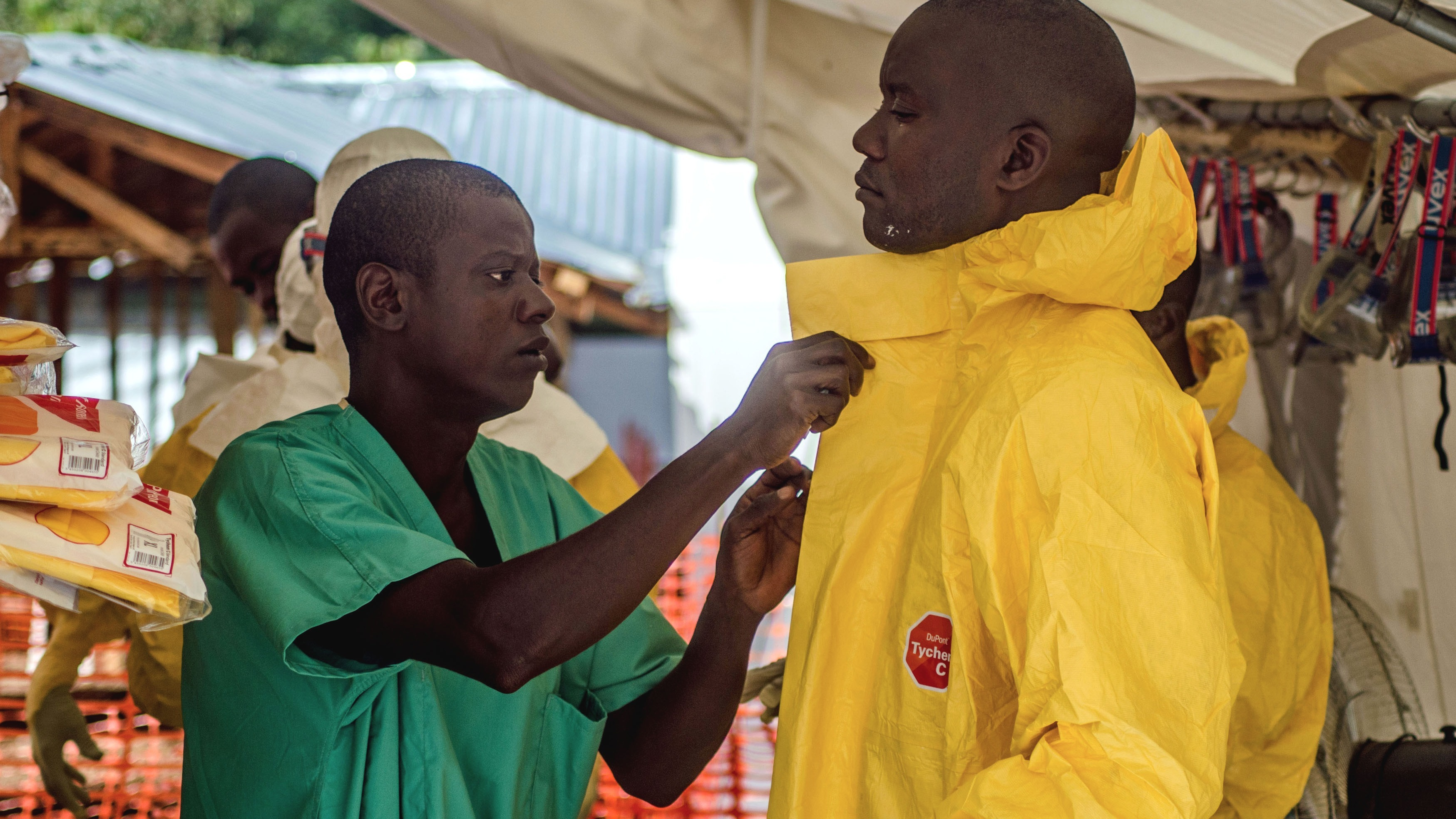 An MSF health worker is dressed in a protective suit before entering the isolation ward at their Kailahun Ebola treatment centre.