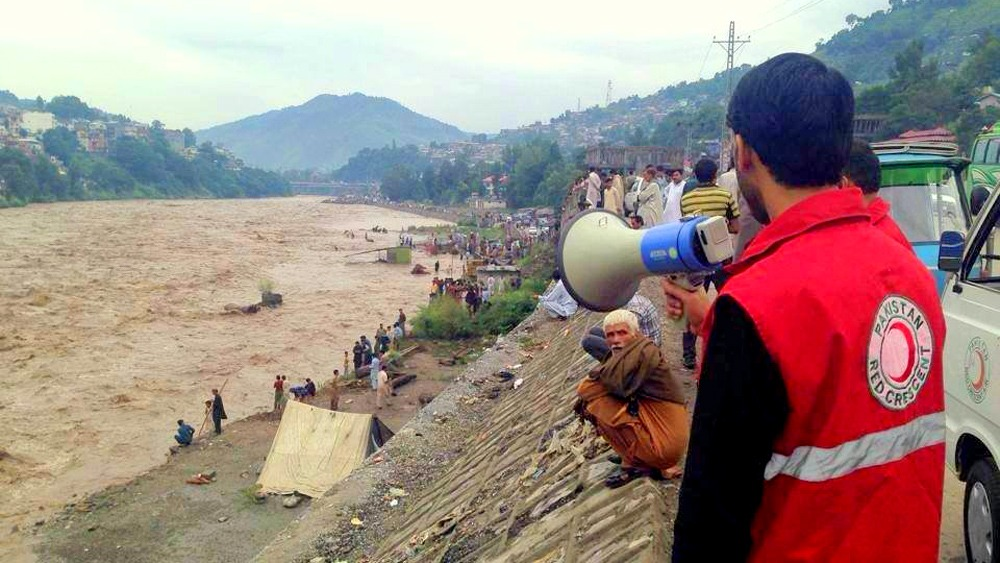A response team member of the Pakistan Red Crescent Society issues an alert on a mega phone to people near the junction of Jhelum and Neelum rivers in Muzaffarabad district.