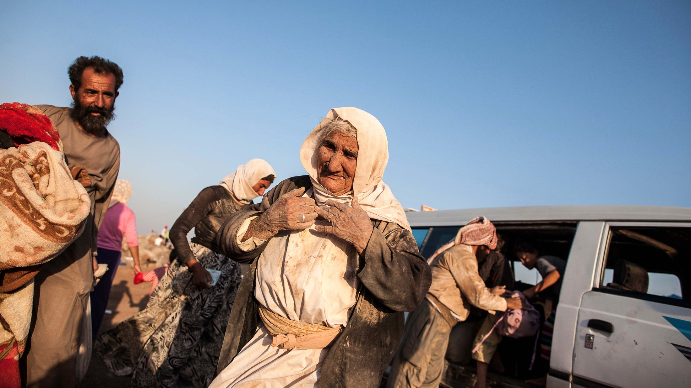 An elderly Yazidi woman arrives with her family into Newroz refugee camp, situated next to the town of al-Malikyah in Rojava, Syria