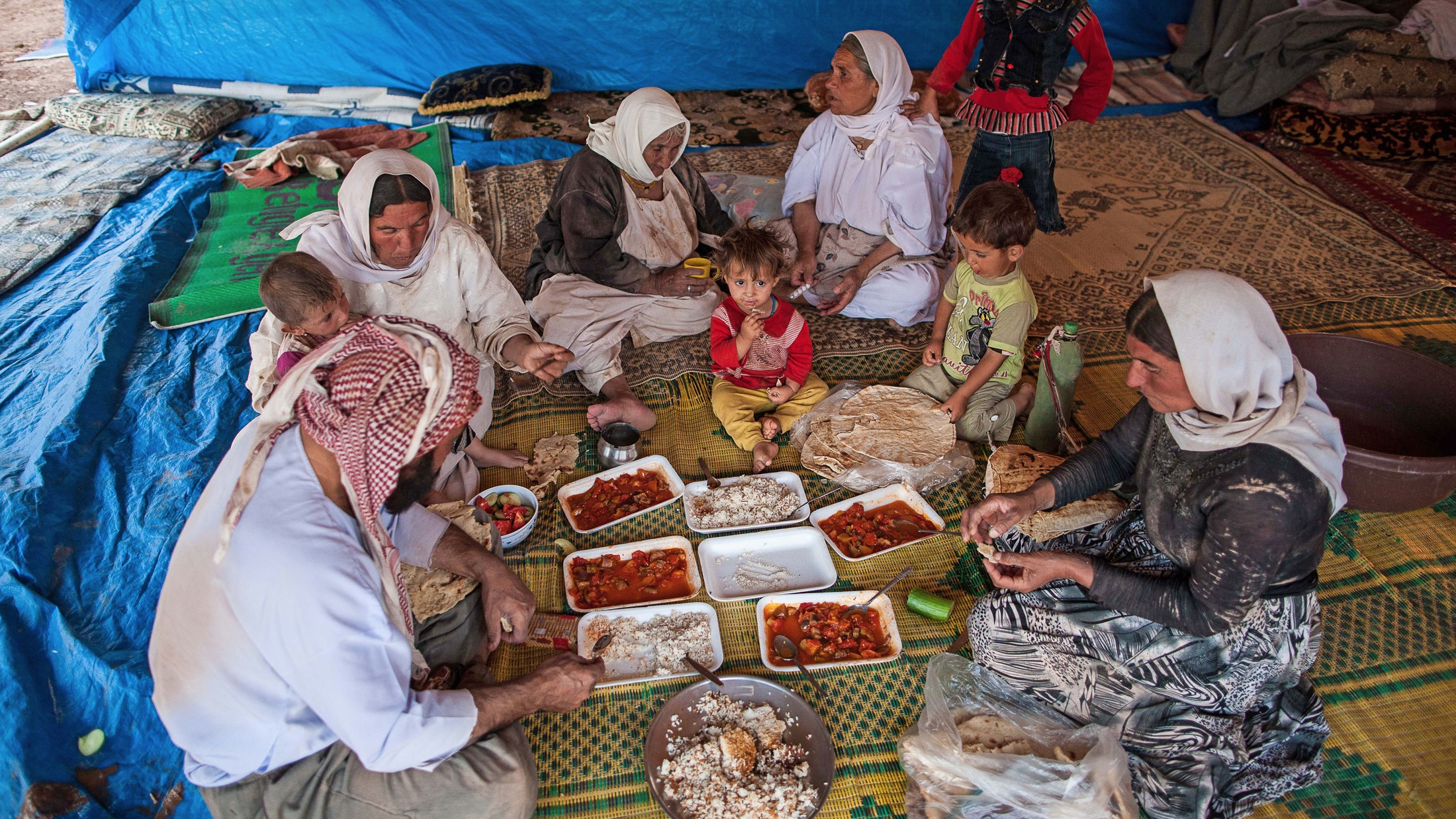 An IDP family shares a meal at Newroz refugee camp, situated next to the town of al-Malikyah in Rojava, Syria