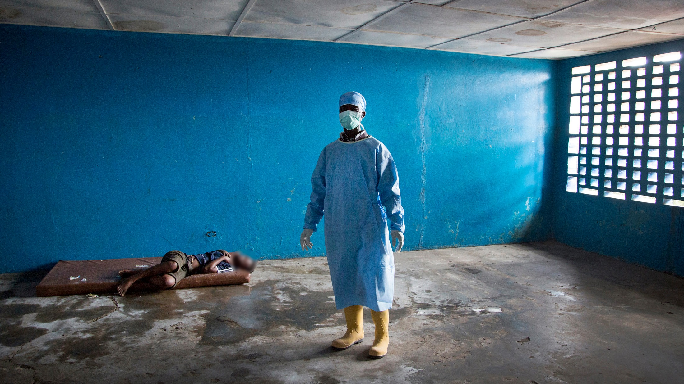 A healthcare worker stands next to a woman who had died of Ebola related symptoms. (Sep 2014)