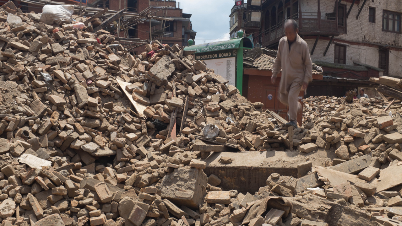 A man walks on top of debris from collapsed monuments in Basantapur in Central Kathmandu on 27 April 2015 in Kathmandu, Nepal. Nepal was struck by a powerful earthquake on 25 April