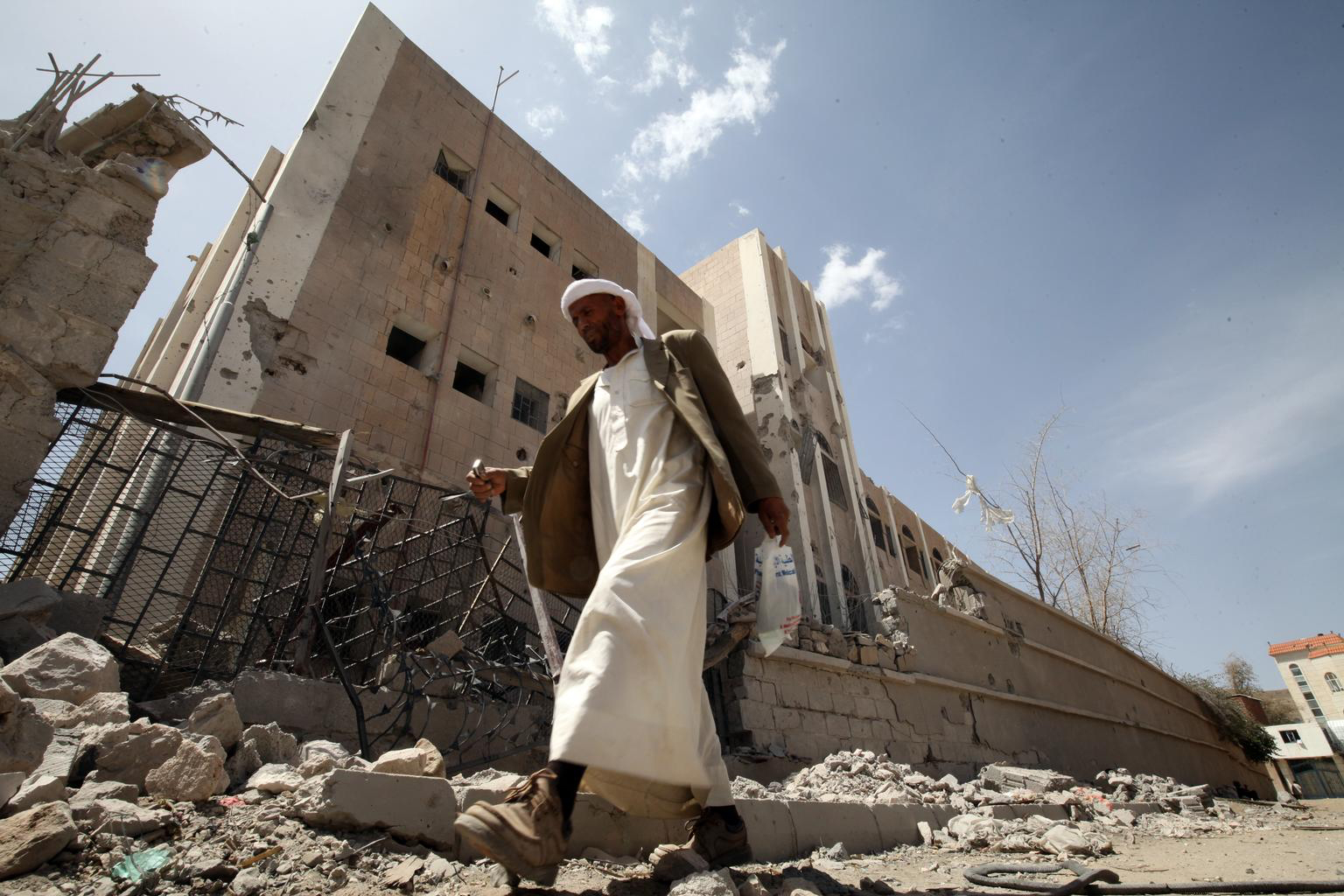 April 28, 2015. A guard walks past what remains of Ibn Sina School, in Sana'a, the capital. The school was heavily damaged during an air strike that hit the building next to the school. The impact of the blast crumbled the outer wall of the schoolyard a