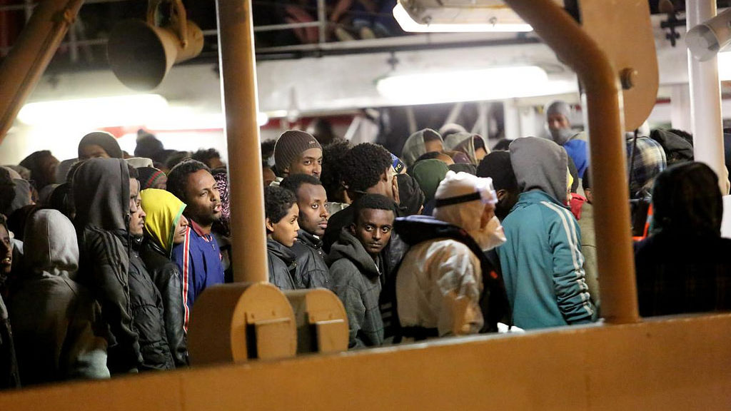 Rescued refugees and migrants wait to leave an Italian Coastguard vessel in Palermo, Italy.